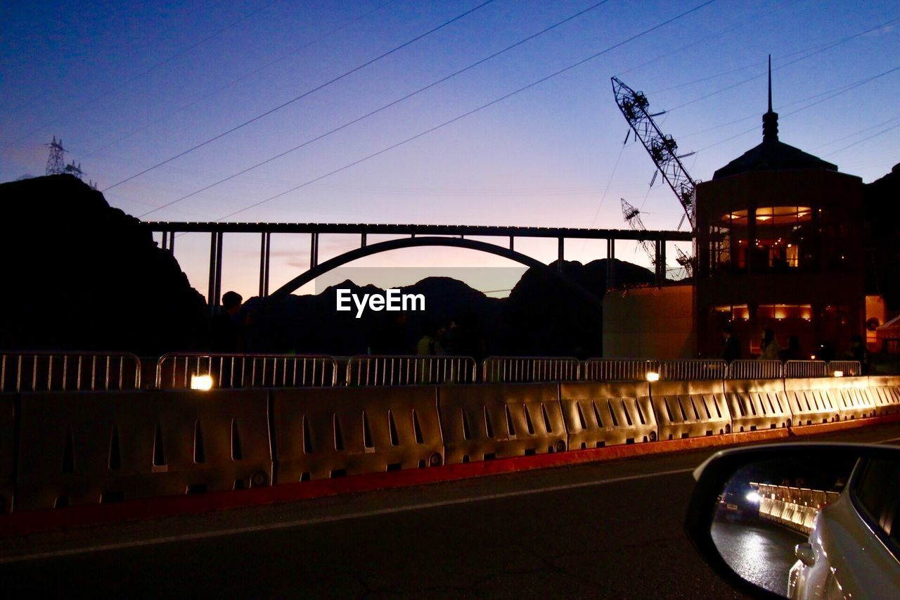 bridge - man made structure, architecture, built structure, connection, transportation, sunset, building exterior, sky, river, land vehicle, outdoors, bridge, city, car, illuminated, water, cable, silhouette, no people, night, travel destinations, road, tree