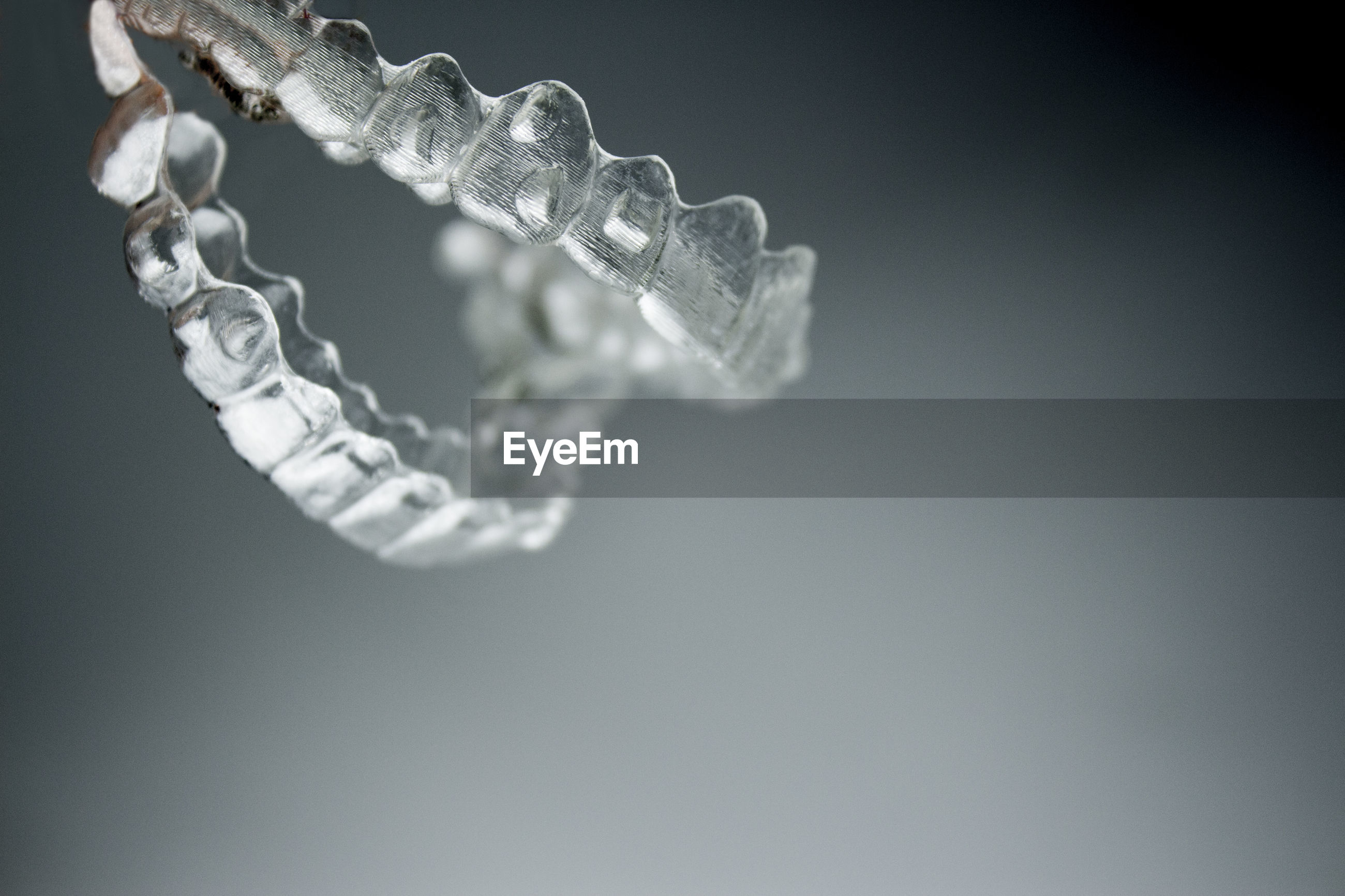Close-up of plastic dentures over gray background