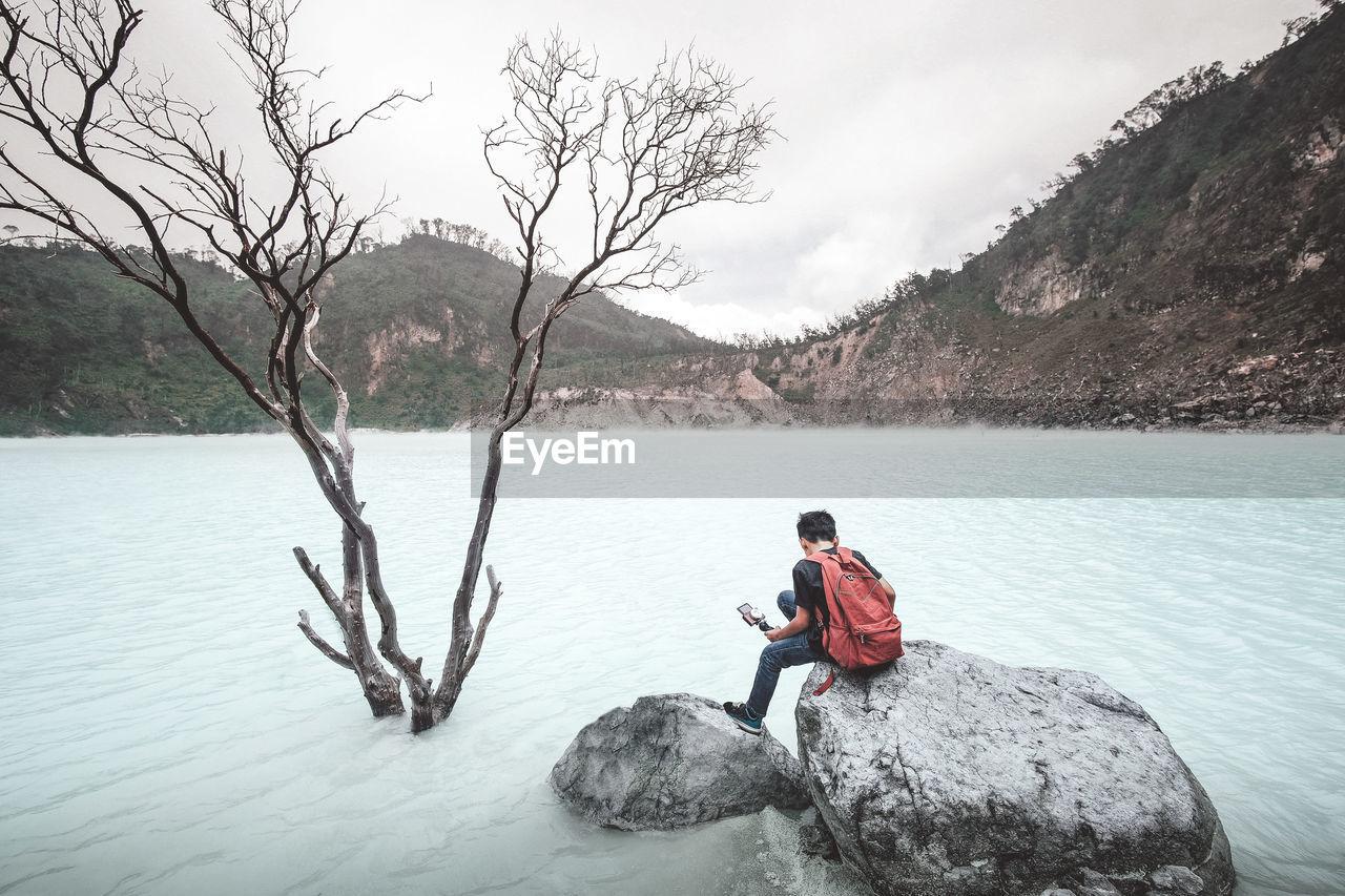 Boy Sitting On Rock At Lake Against Mountains