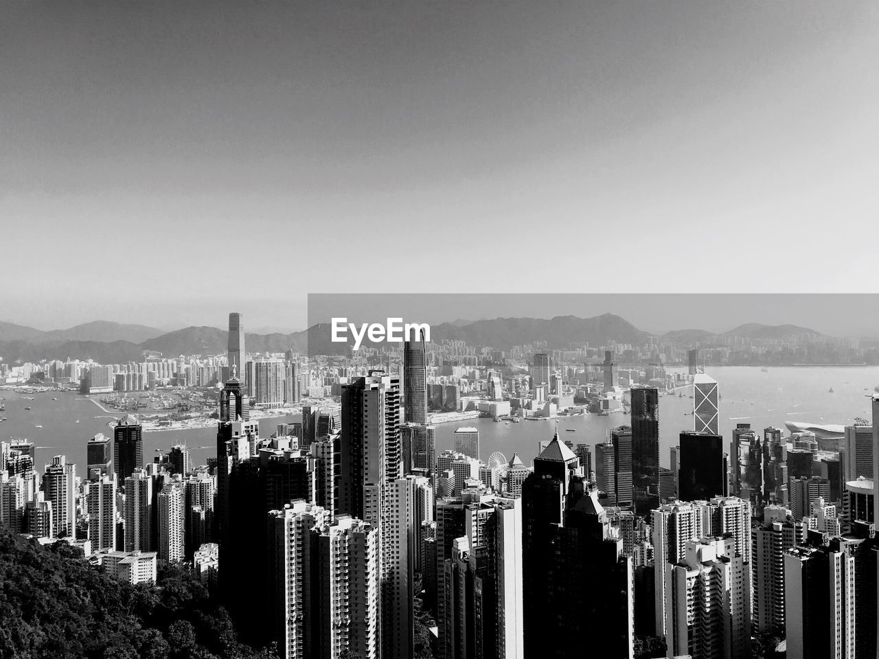 cityscape, skyscraper, architecture, city, crowded, mountain, building exterior, modern, built structure, outdoors, travel destinations, urban skyline, clear sky, day, nature, sky