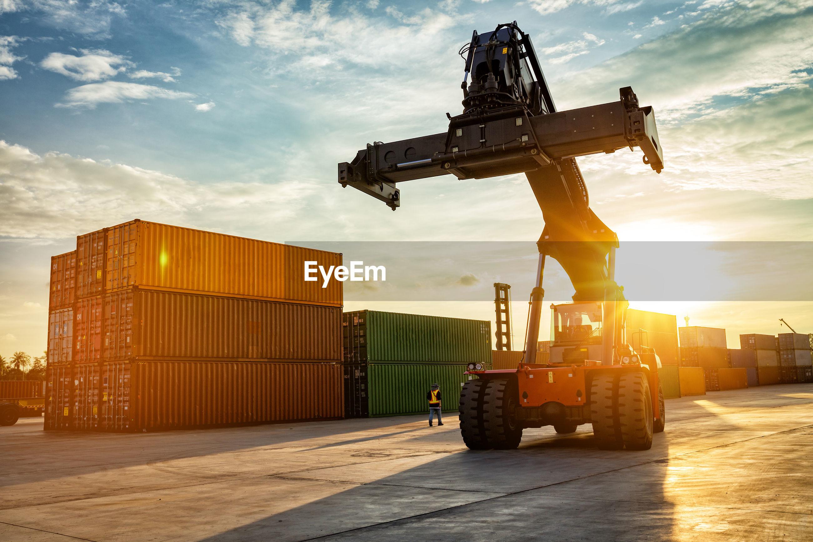 Forklift on shipping port against sky