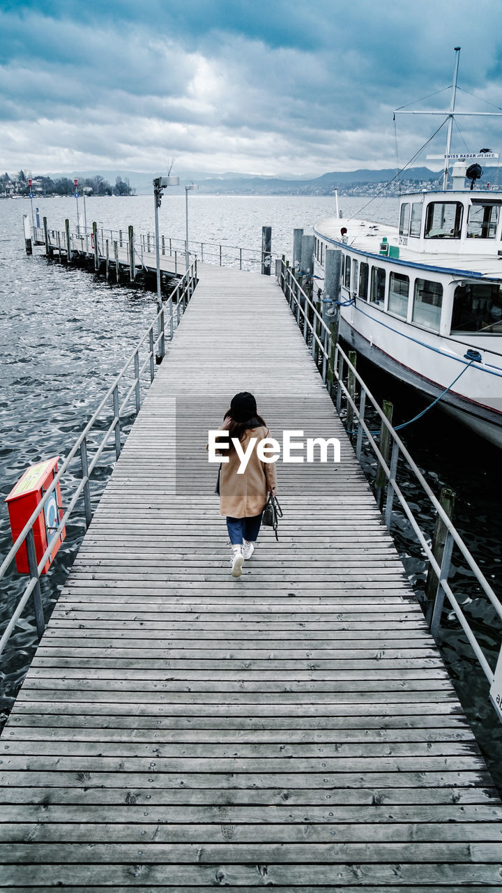 Rear View Of Woman Walking On Pier Over Sea