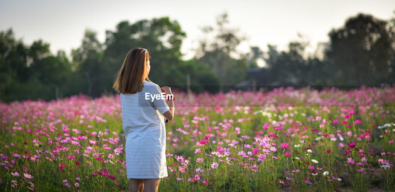 Woman Standing Against Flowering Plants