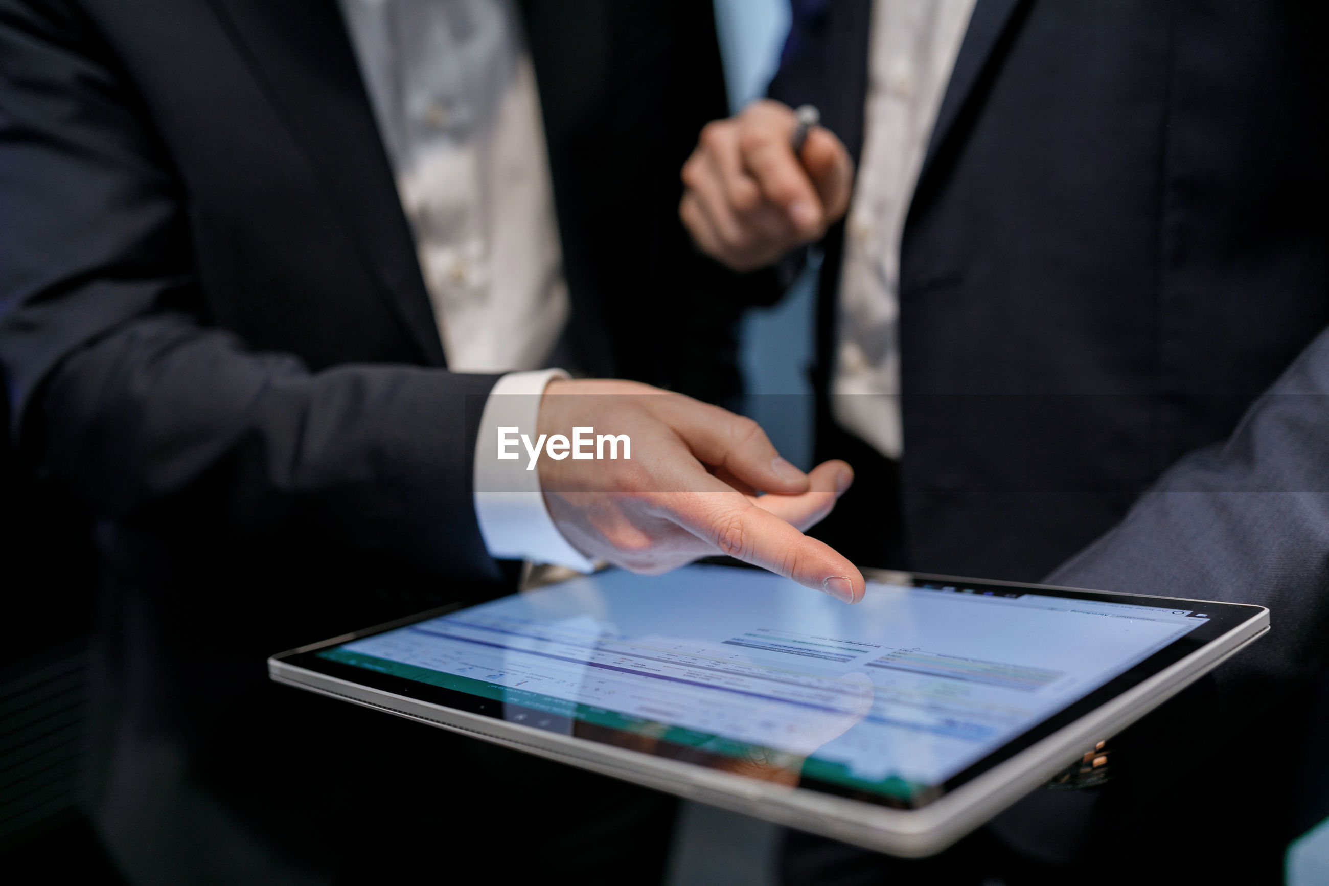 Midsection of colleagues discussing over digital tablet
