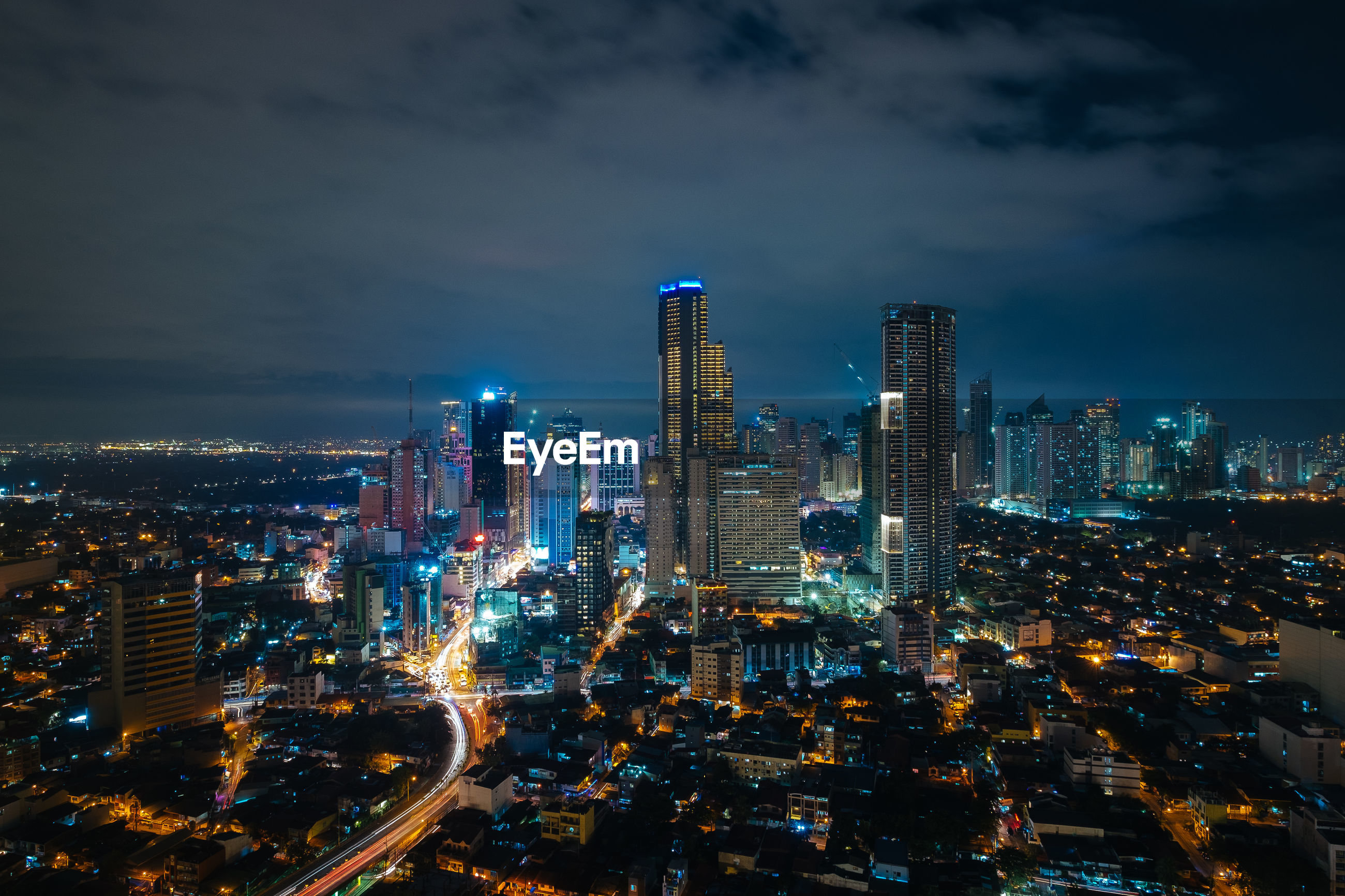 AERIAL VIEW OF ILLUMINATED CITYSCAPE AGAINST SKY