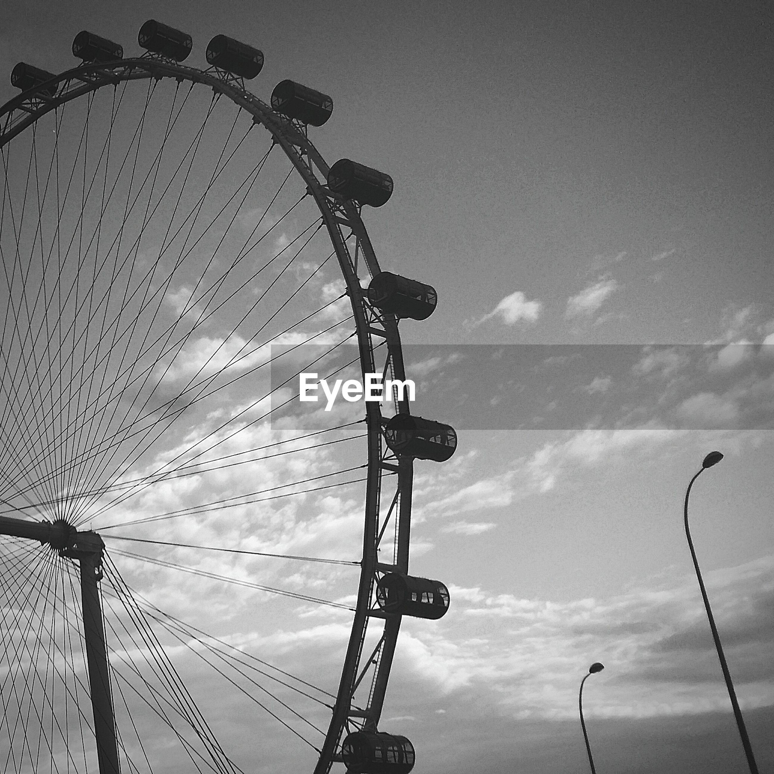 ferris wheel, amusement park, amusement park ride, arts culture and entertainment, low angle view, sky, silhouette, tall - high, outdoors, dusk, metal, enjoyment, big wheel, cloud - sky, fairground, chain swing ride, fun, cloud, large, no people
