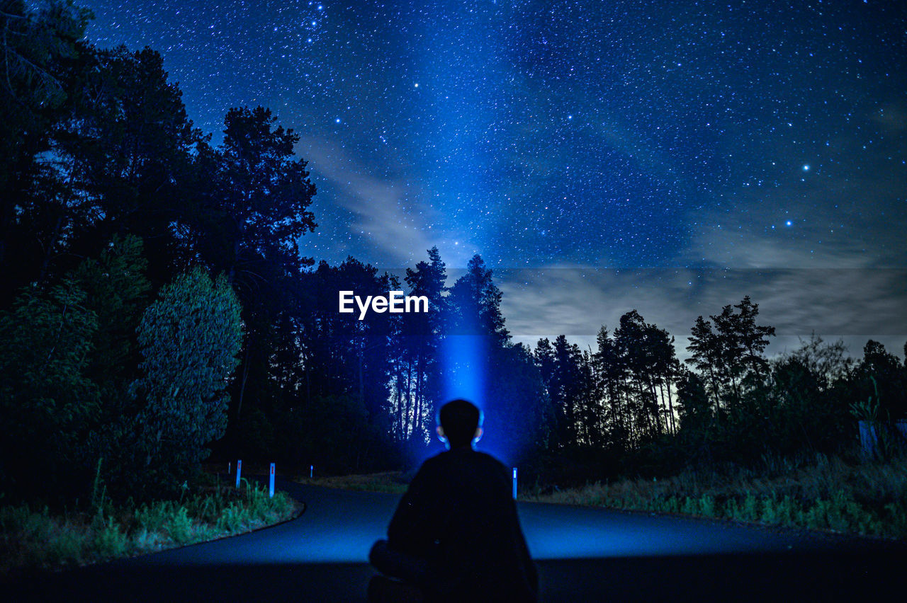 Rear view of person holding flashlight sitting against trees at night