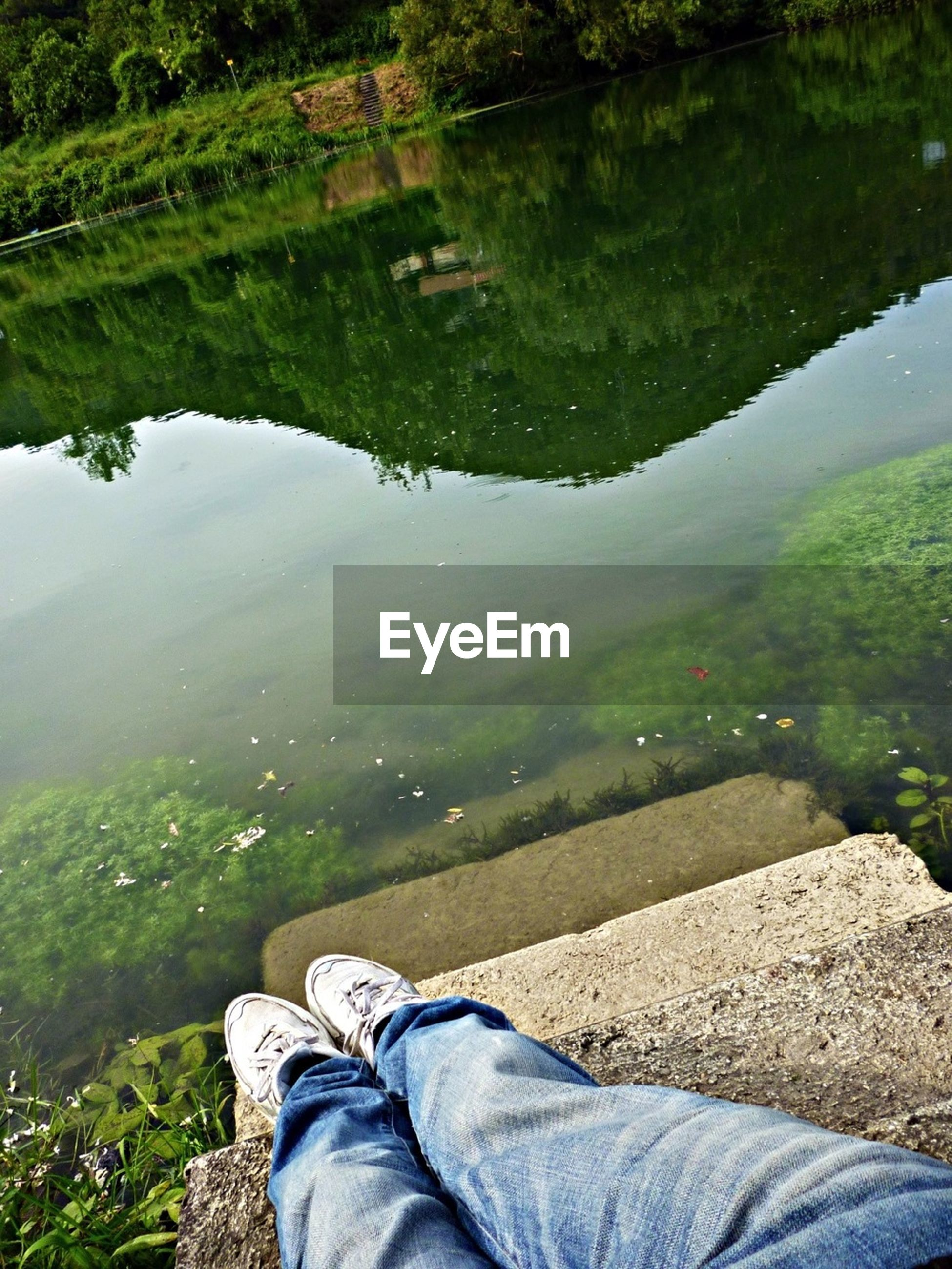 water, low section, person, lake, grass, tranquility, personal perspective, relaxation, tranquil scene, leisure activity, shoe, nature, lifestyles, reflection, men, beauty in nature, high angle view, scenics