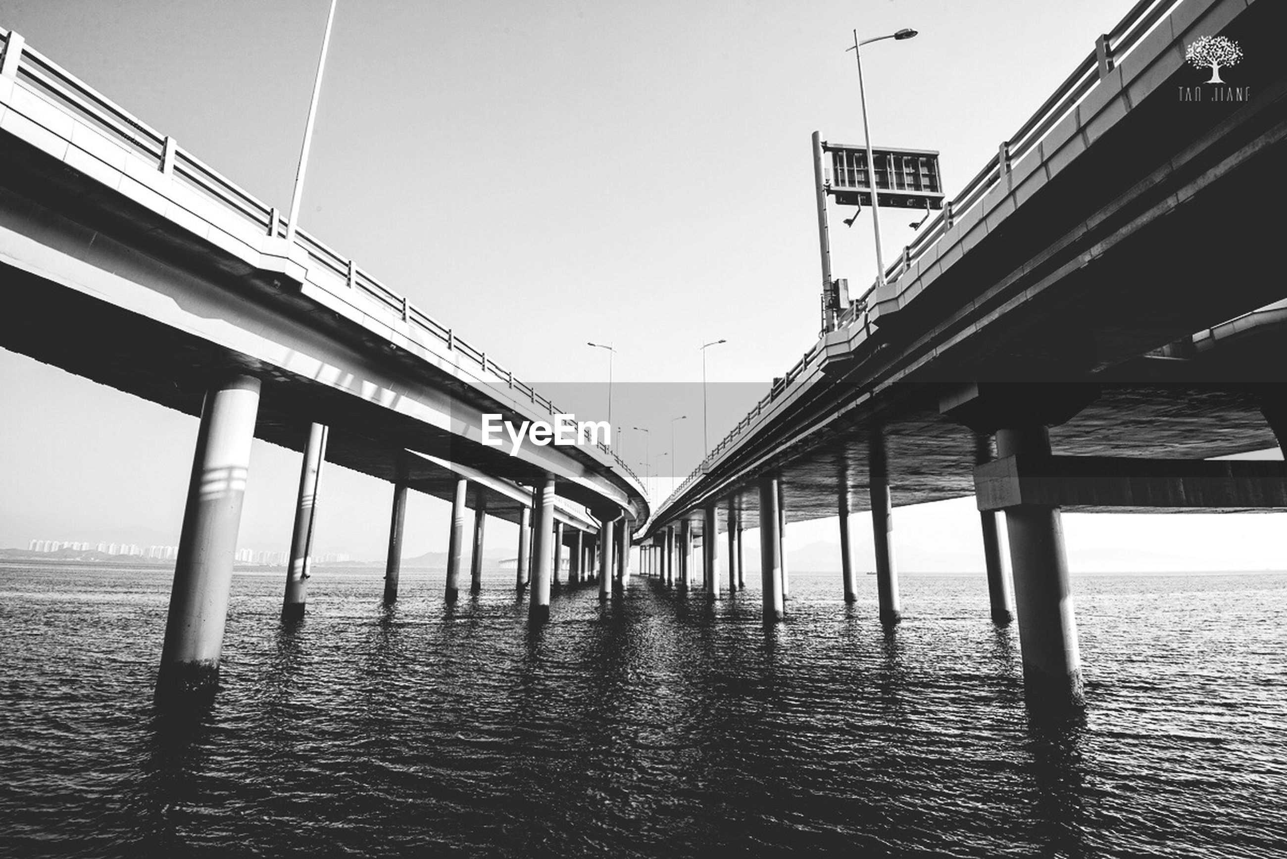 water, built structure, connection, architecture, sea, bridge - man made structure, bridge, clear sky, waterfront, pier, engineering, long, transportation, sky, support, low angle view, rippled, railing, diminishing perspective, no people
