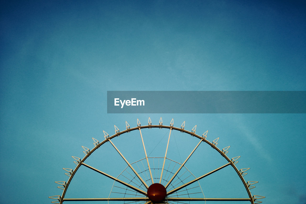 sky, amusement park ride, amusement park, arts culture and entertainment, low angle view, blue, nature, architecture, day, copy space, no people, built structure, clear sky, ferris wheel, outdoors, high section, carousel, carnival, semi-circle, enjoyment