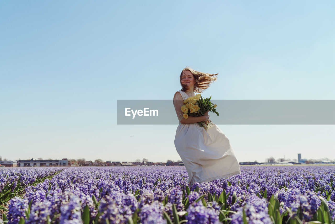 Rear view of woman with flowers on field against clear sky