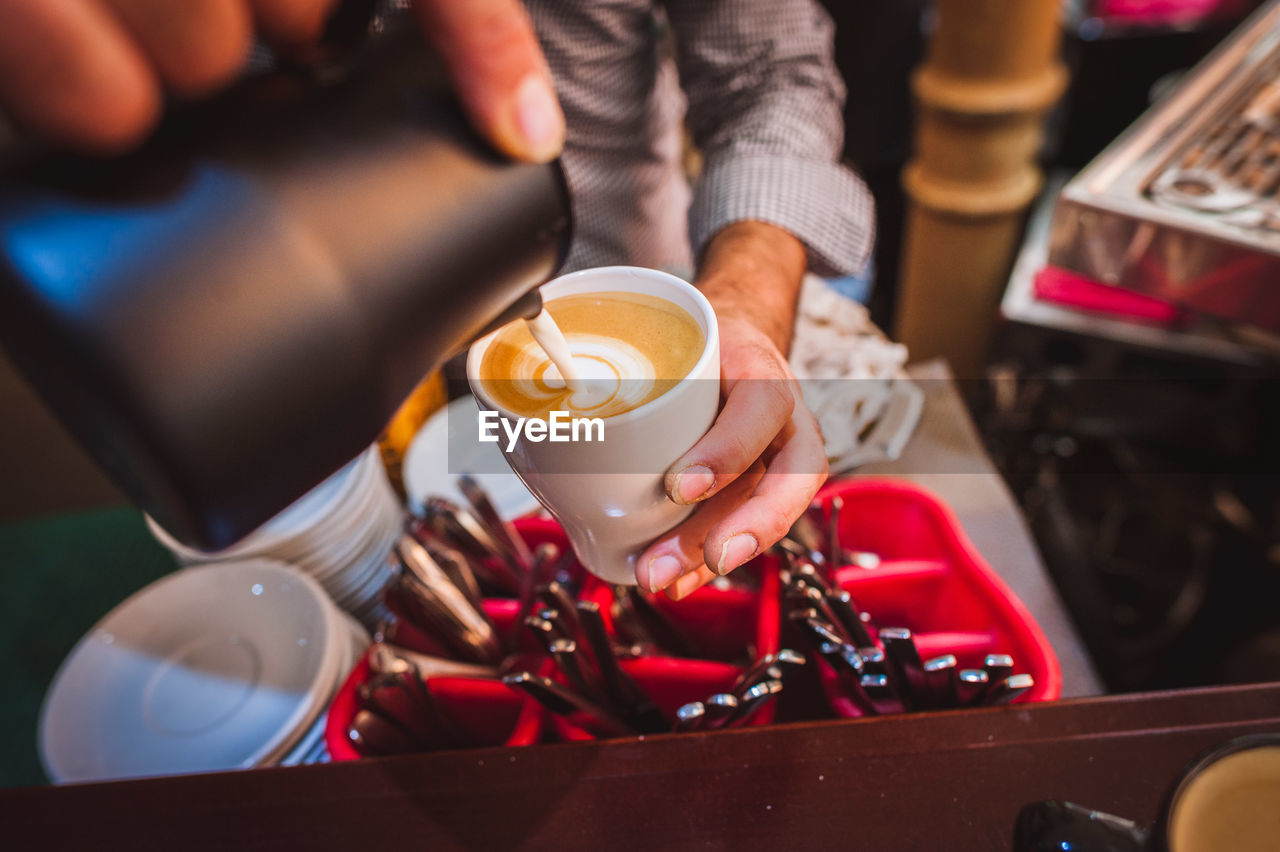 food and drink, coffee, coffee - drink, cup, drink, coffee cup, refreshment, mug, real people, barista, holding, one person, cafe, occupation, midsection, business, coffee shop, indoors, focus on foreground, adult, frothy drink, preparation, hand, cafe culture, latte