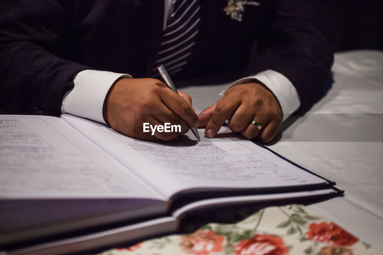 Cropped Image Of Groom Signing Wedding Papers