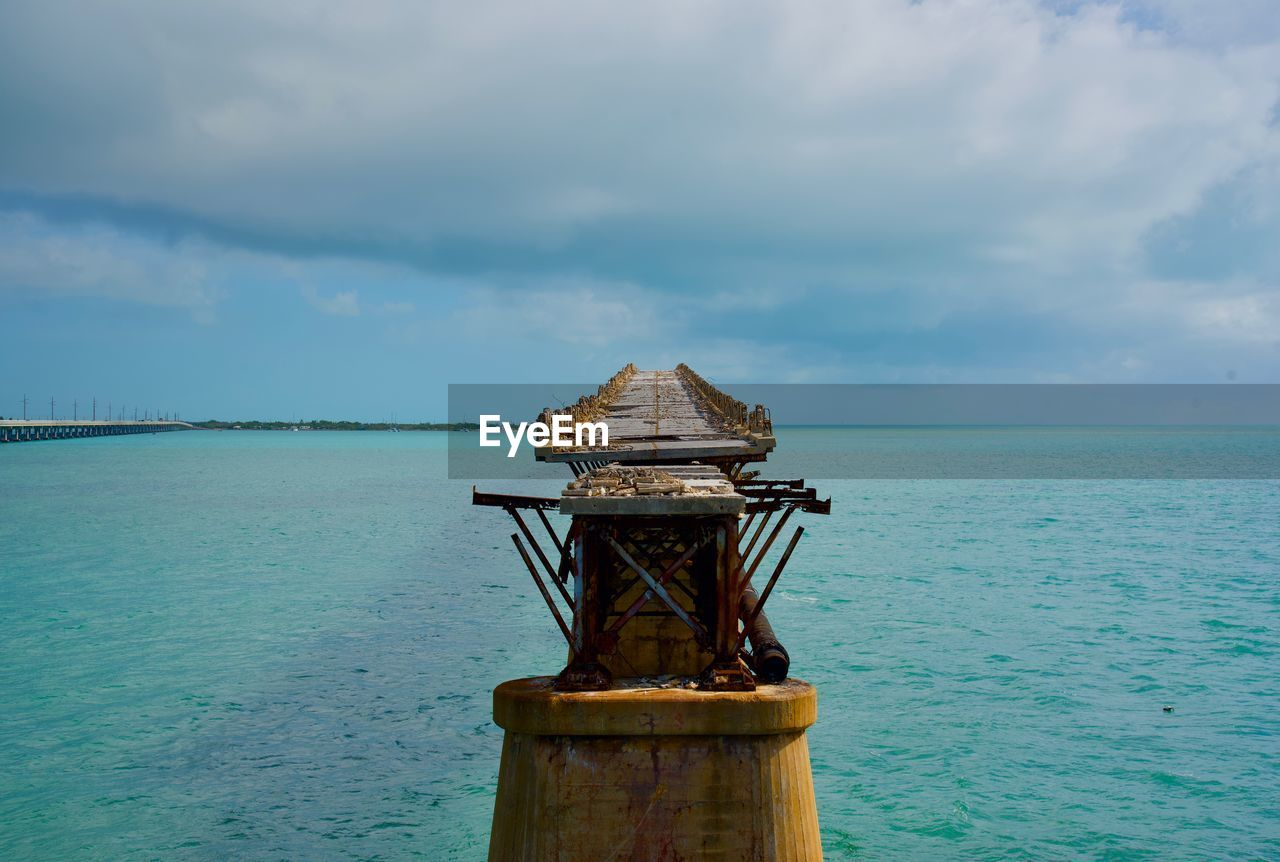 water, sky, cloud - sky, sea, scenics - nature, beauty in nature, tranquil scene, nature, no people, horizon over water, tranquility, day, horizon, non-urban scene, outdoors, architecture, idyllic, built structure, wood - material, post, turquoise colored, wooden post
