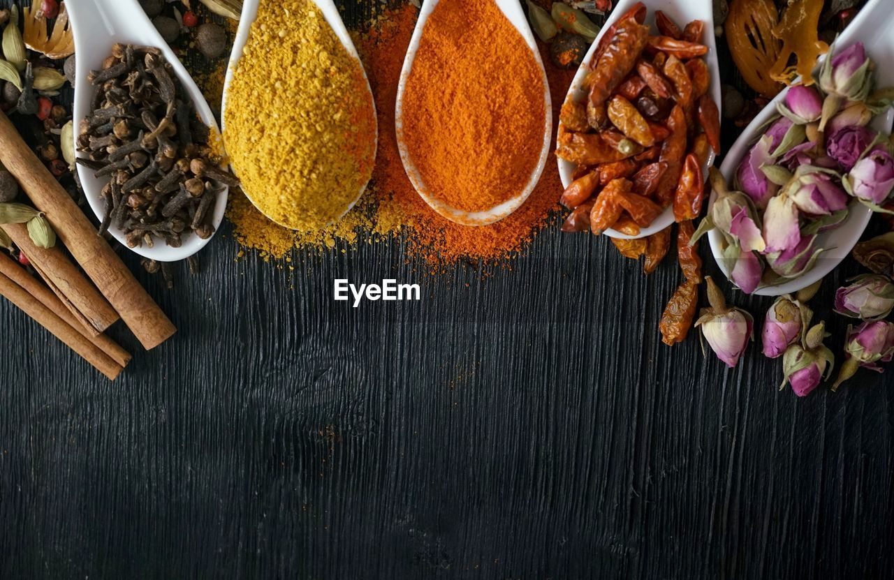 food and drink, food, freshness, table, spice, indoors, variation, ingredient, choice, still life, high angle view, wood - material, no people, vegetable, cinnamon, directly above, close-up, plant, wellbeing, kitchen utensil, cardamom