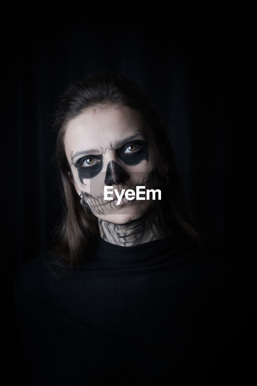 Portrait Of Woman With Make-Up During Halloween Against Black Background