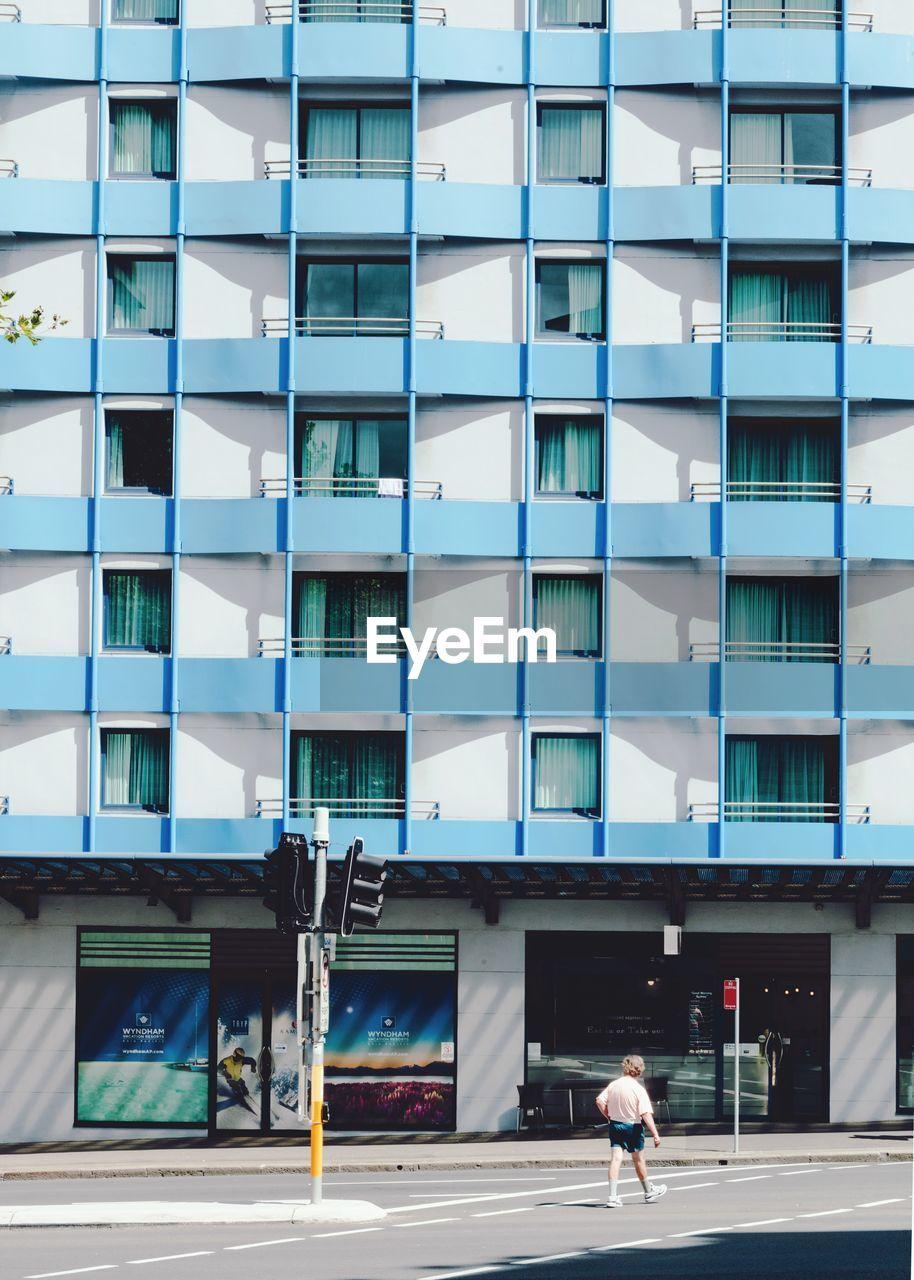 REAR VIEW OF WOMAN WALKING ON STREET AGAINST MODERN BUILDINGS