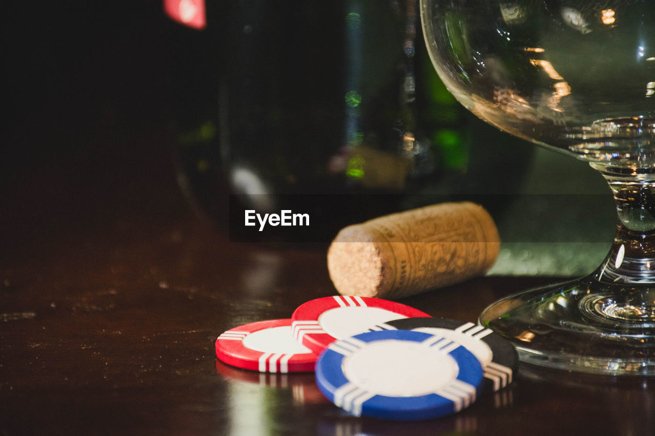 Close-Up Of Gambling Chips By Wine Bottle On Table At Casino