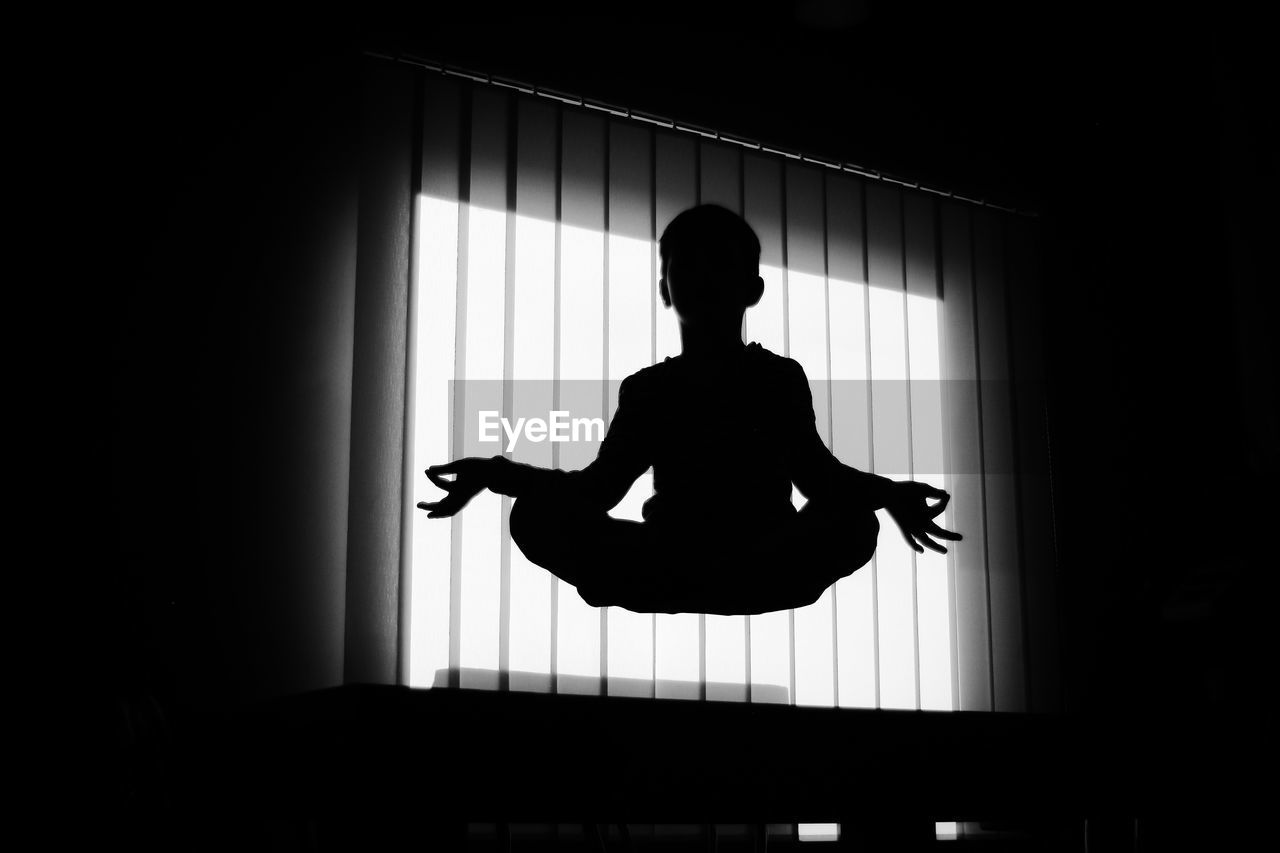 Silhouette Boy Meditation In Mid-Air