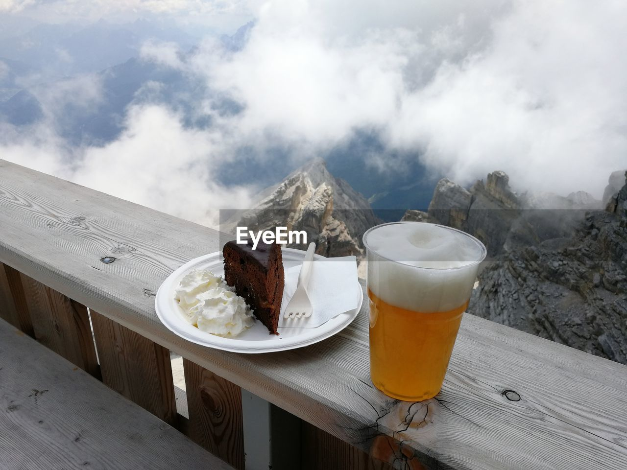 Cake and beer on table against mountains
