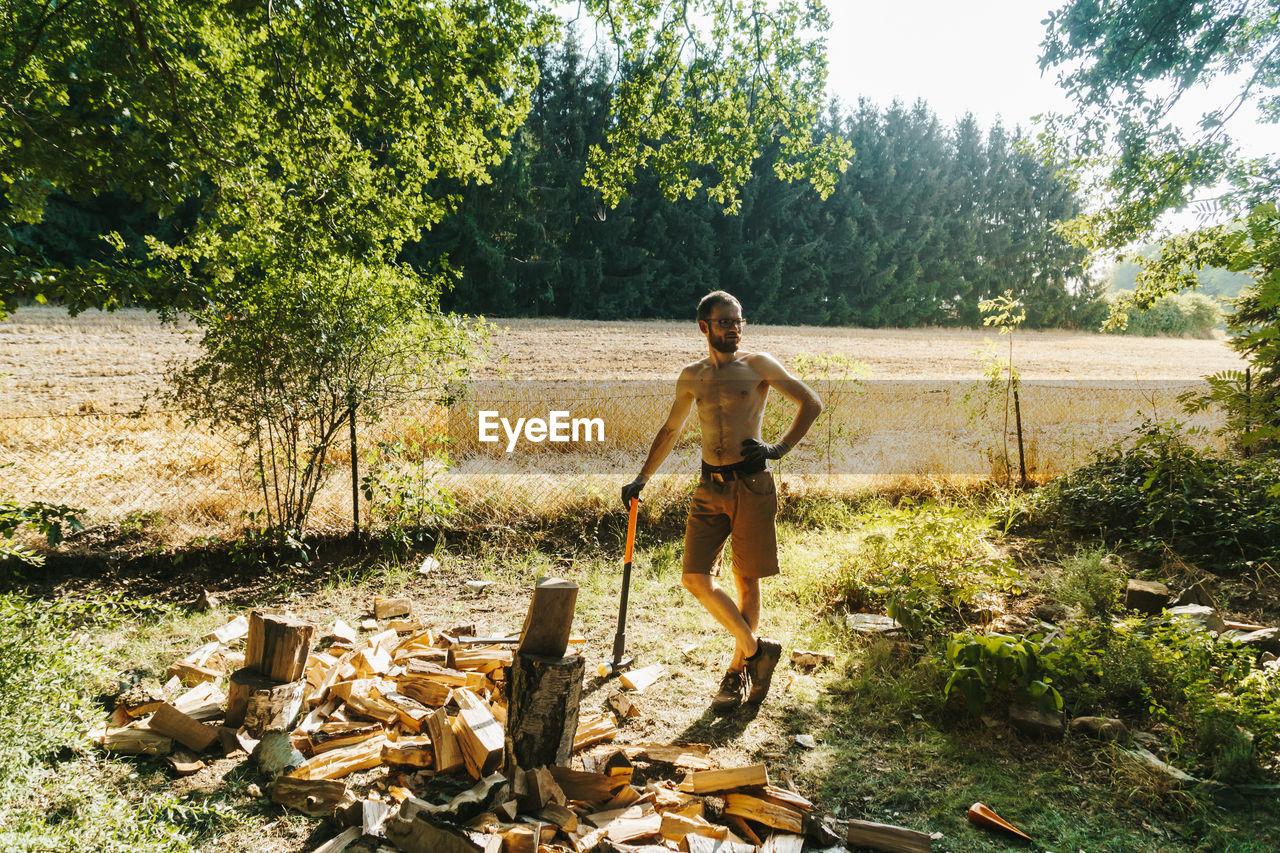 Full length of shirtless lumberjack standing by wood on field