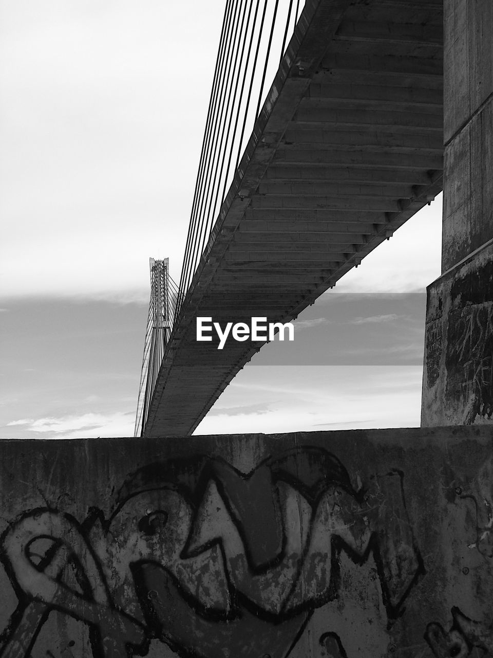 architecture, built structure, bridge, sky, bridge - man made structure, graffiti, text, no people, low angle view, western script, nature, connection, day, wall - building feature, building exterior, communication, wall, transportation, outdoors, cloud - sky