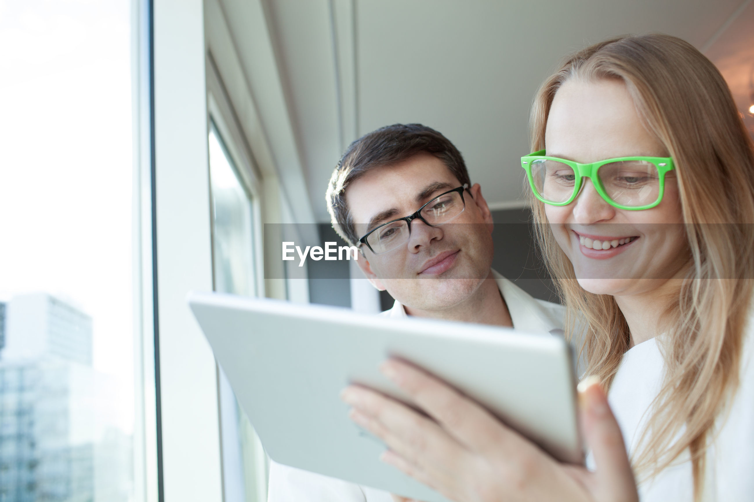 Happy couple using digital tablet by window