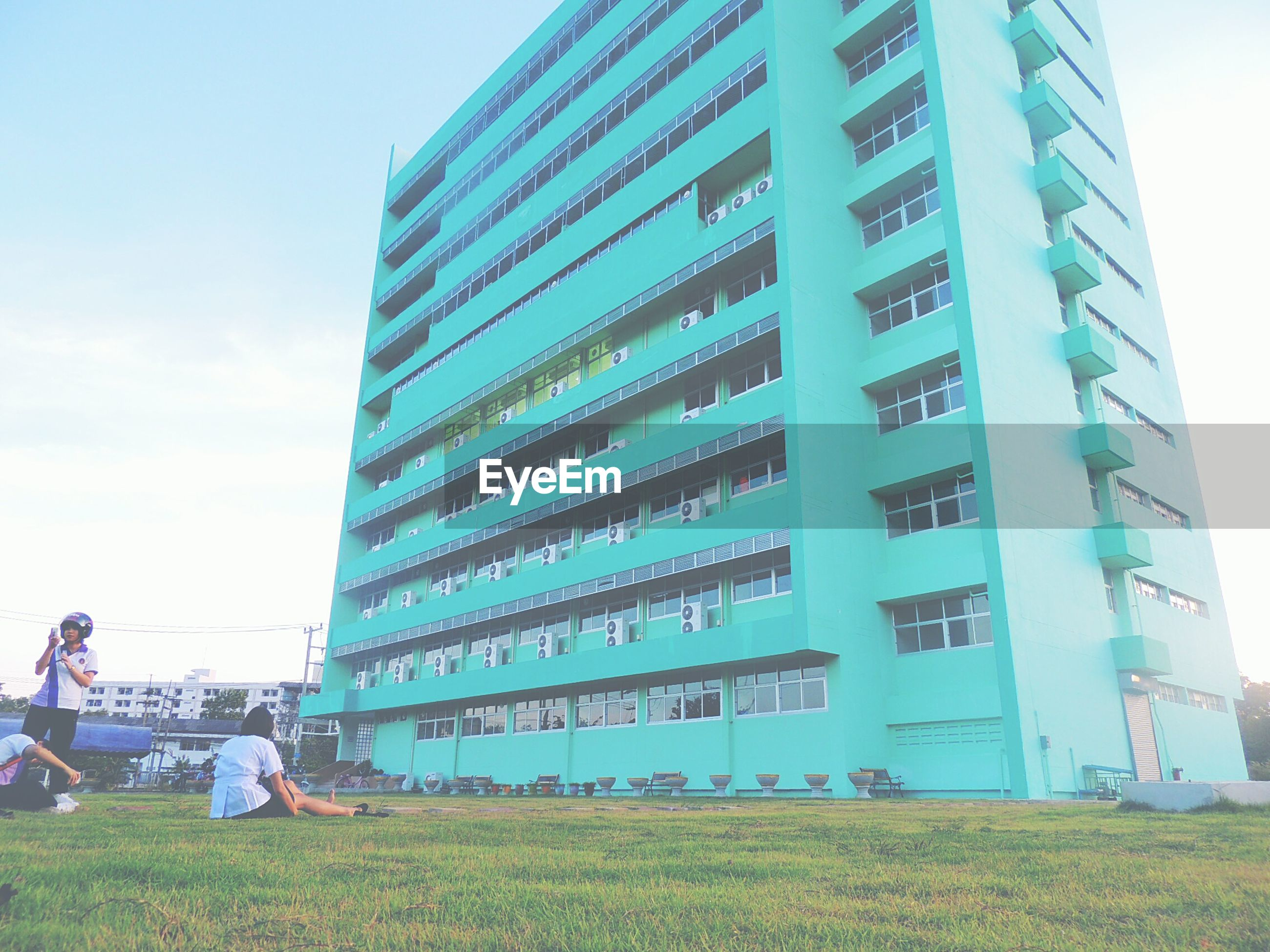 building exterior, architecture, built structure, modern, office building, city, low angle view, building, sky, men, skyscraper, tall - high, tower, lifestyles, city life, day, grass, leisure activity, blue
