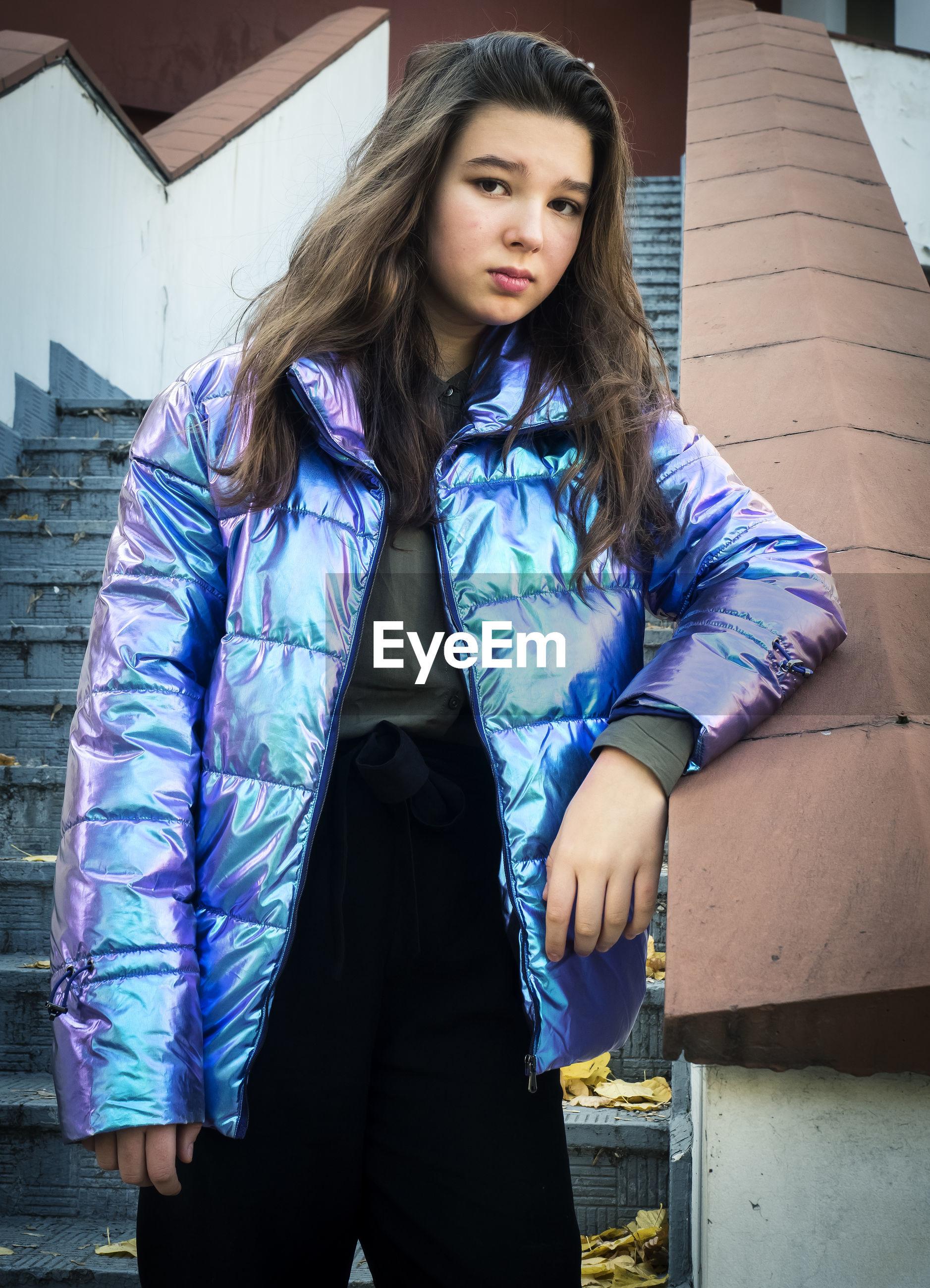 Portrait of teenage girl standing on steps