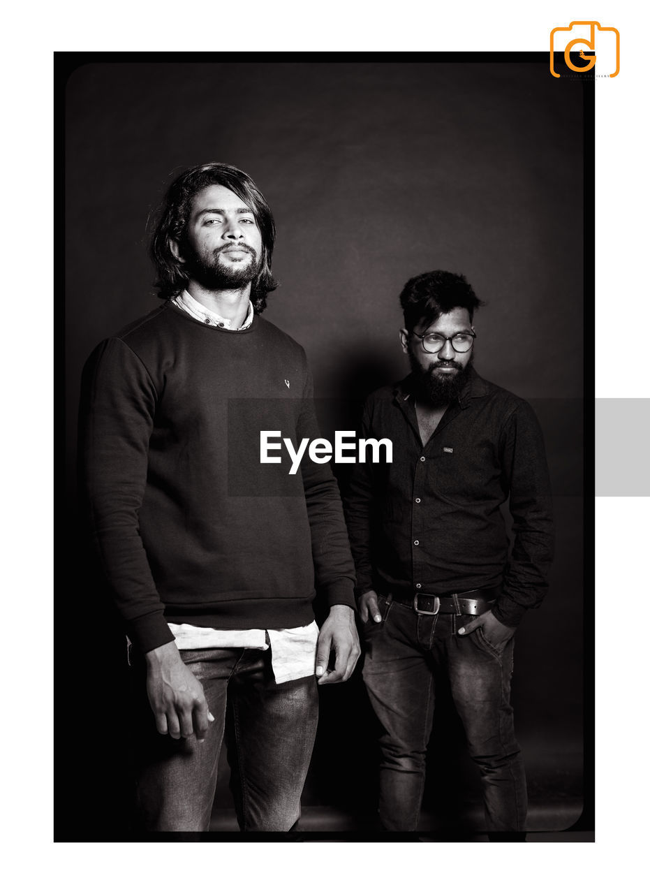 looking at camera, portrait, two people, studio shot, front view, standing, real people, hands in pockets, young men, togetherness, young adult, men, indoors, eyeglasses, friendship, day, people