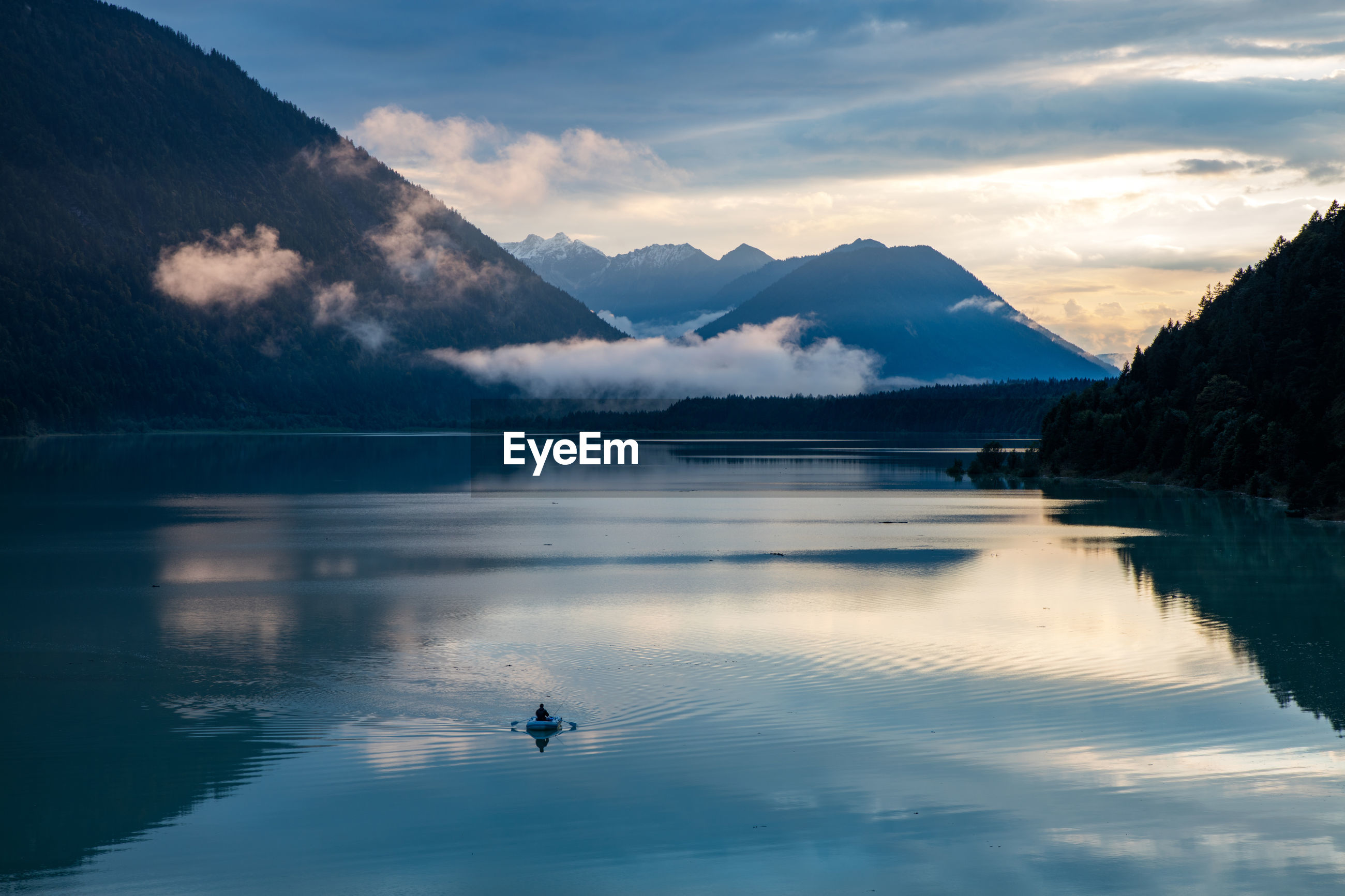 Scenic view of sea and mountains against sky at dusk