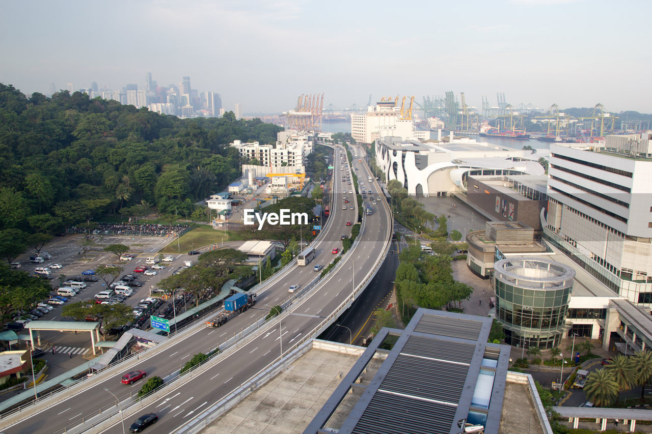 architecture, built structure, building exterior, city, high angle view, transportation, road, tree, cityscape, sky, day, nature, plant, building, connection, mode of transportation, highway, outdoors, no people, bridge, multiple lane highway, office building exterior, skyscraper