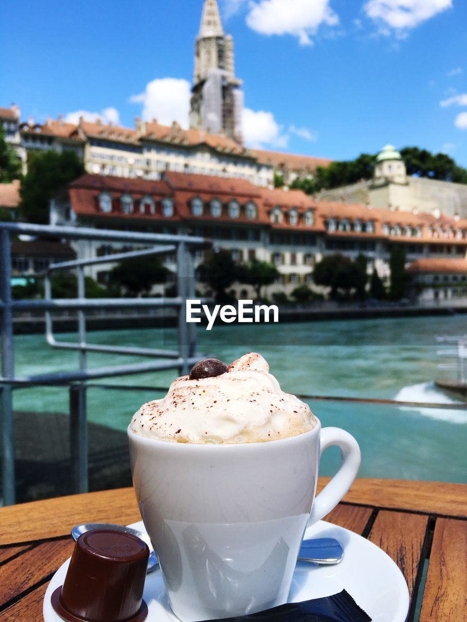 Close-Up Of Coffee With Whipped Cream By Buildings In Background
