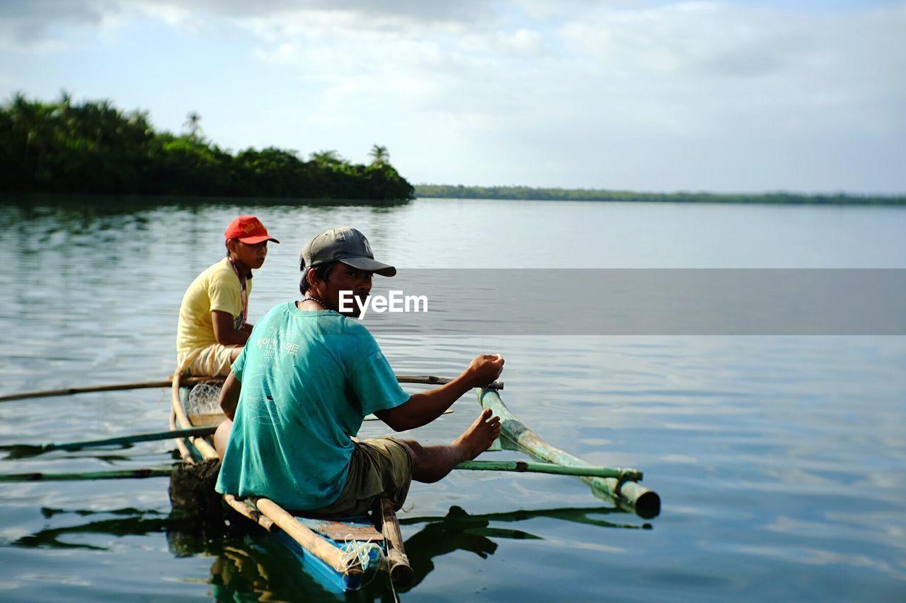 Men boating on lake