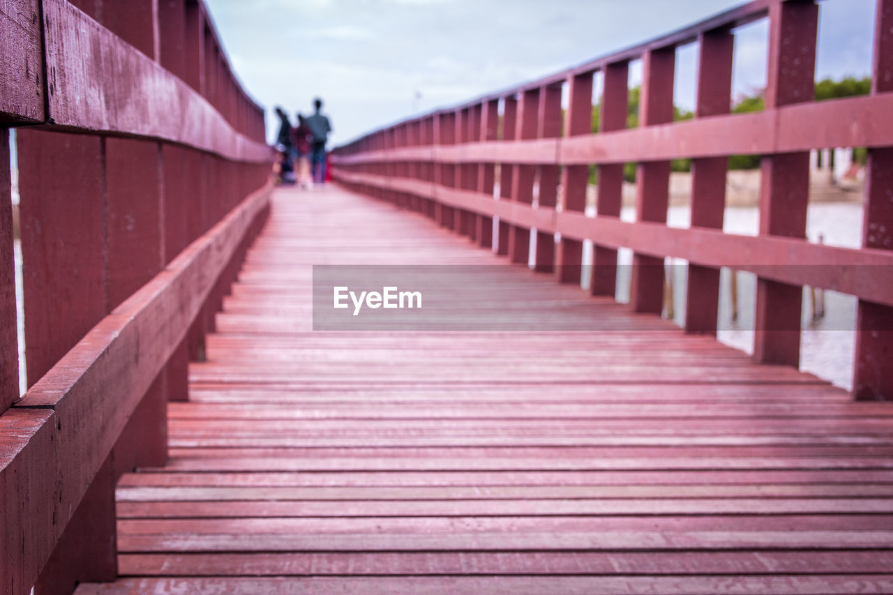 architecture, direction, the way forward, built structure, railing, bridge, lifestyles, real people, one person, bridge - man made structure, connection, day, incidental people, walking, women, nature, outdoors, sky, leisure activity, diminishing perspective, footbridge