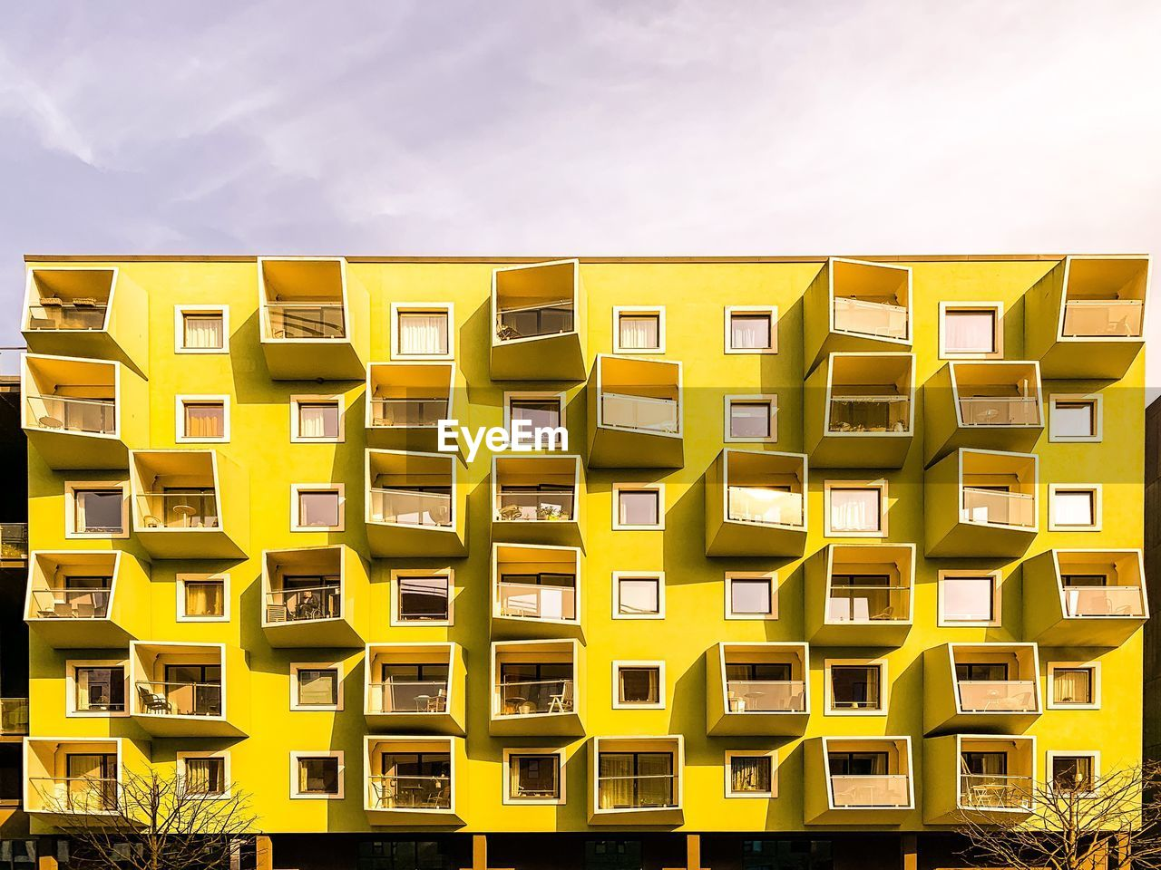 built structure, sky, building exterior, yellow, architecture, no people, residential district, building, city, nature, day, repetition, modern, outdoors, cloud - sky, pattern, balcony, low angle view, side by side, window, apartment, place