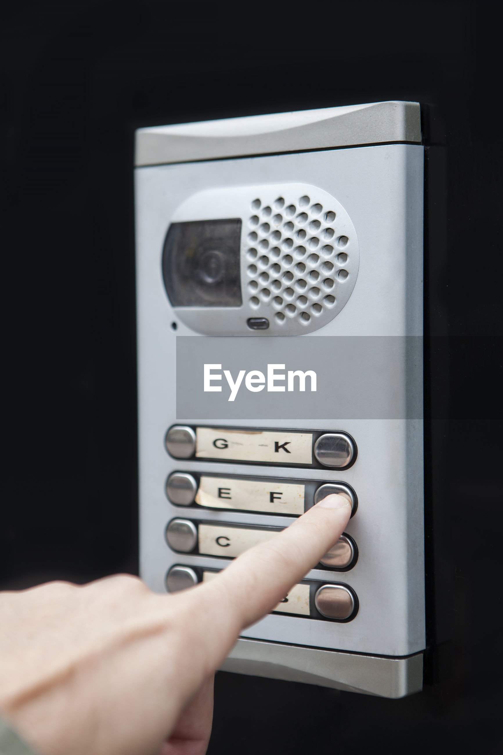 Close-up of hand using security camera against black background