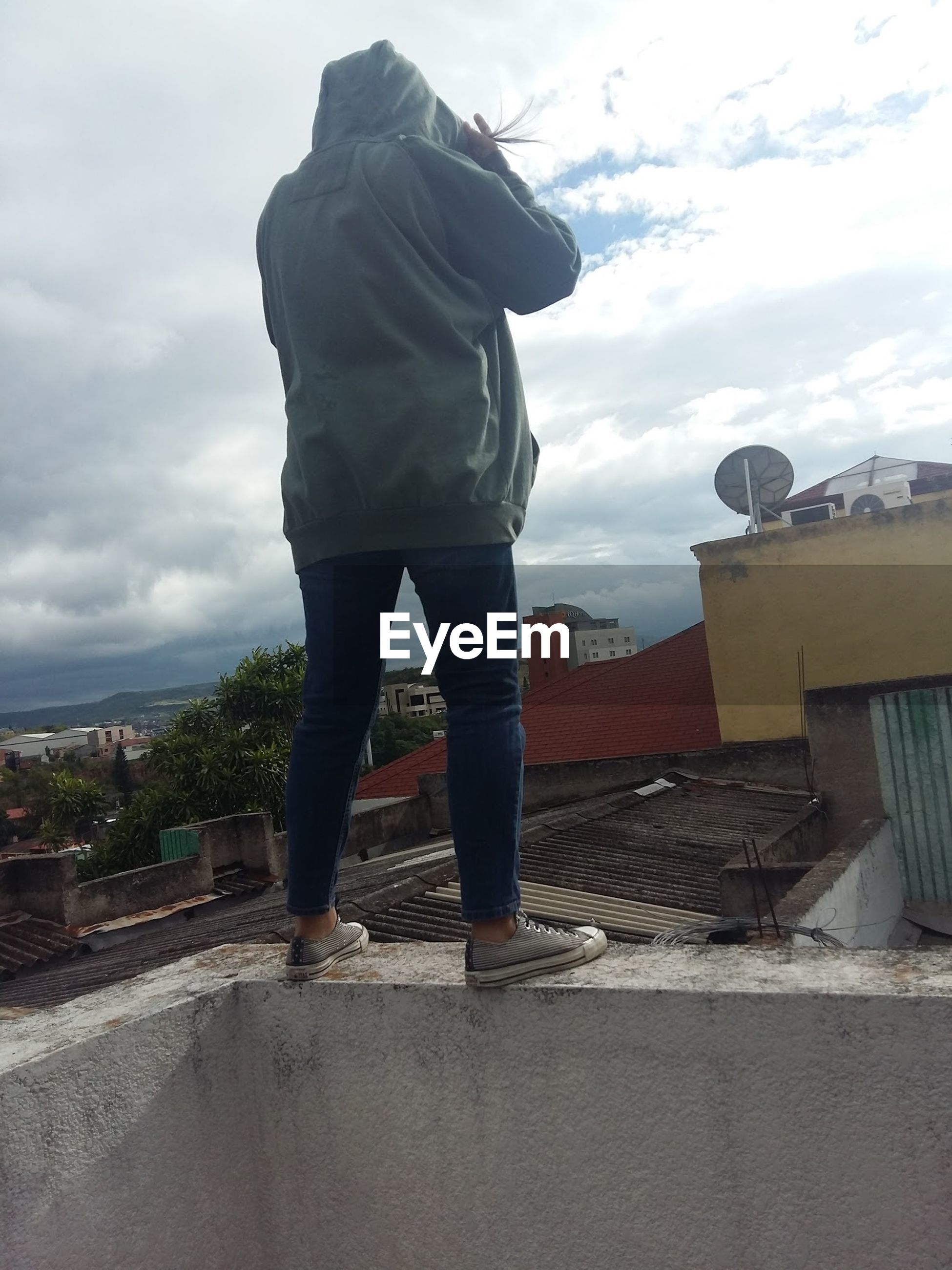 Rear view of woman standing on retaining wall against sky at terrace