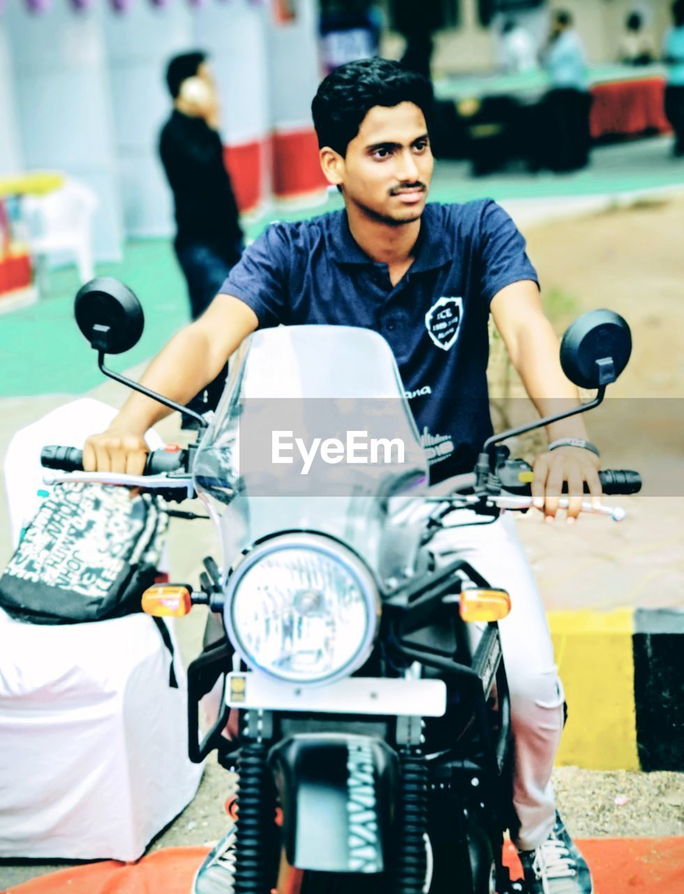 real people, motorcycle, young men, one person, transportation, men, focus on foreground, young adult, mode of transportation, front view, scooter, leisure activity, casual clothing, lifestyles, portrait, three quarter length, sitting, land vehicle, looking, riding