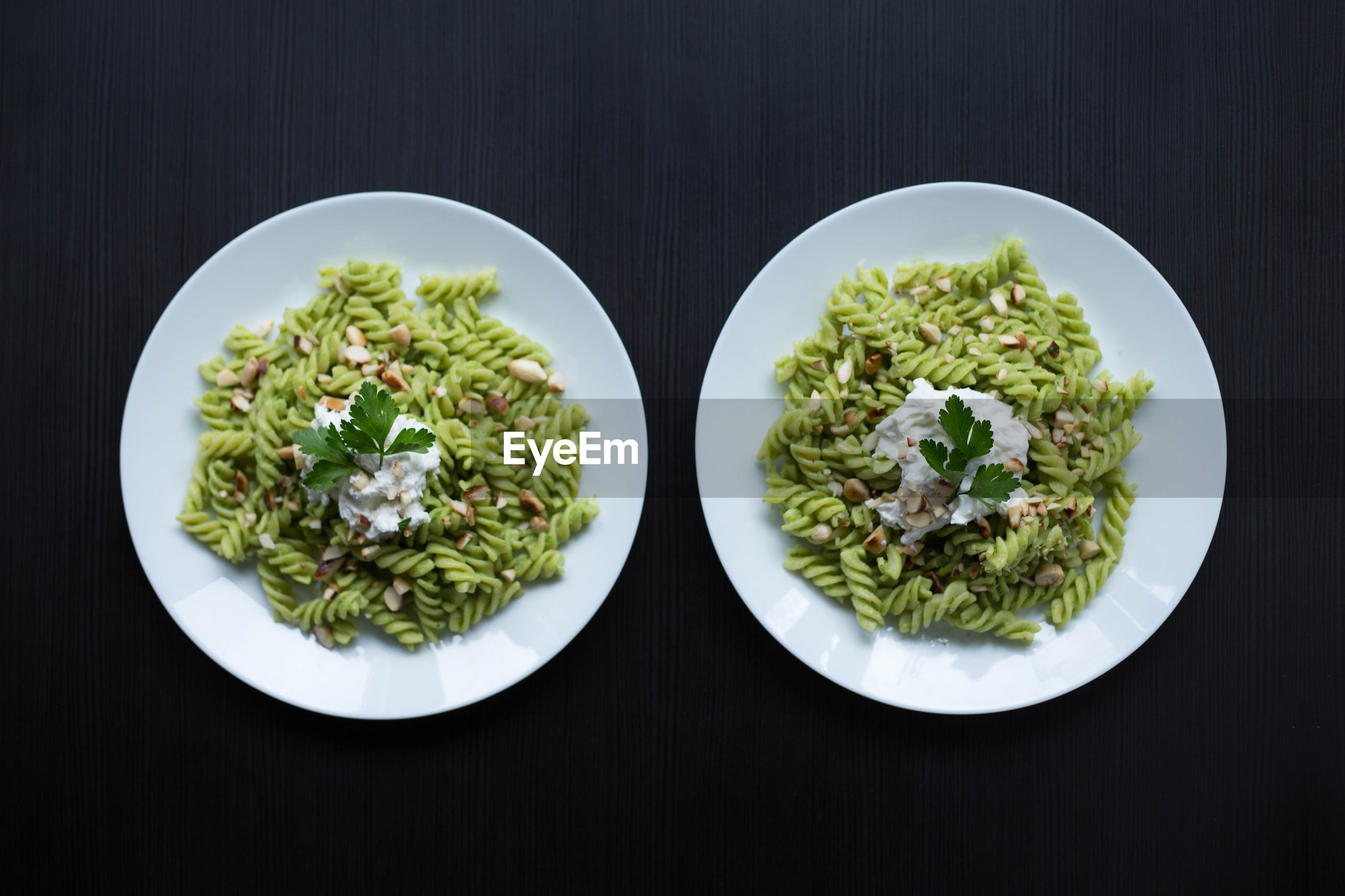 Close-up of served green pasta on two plates