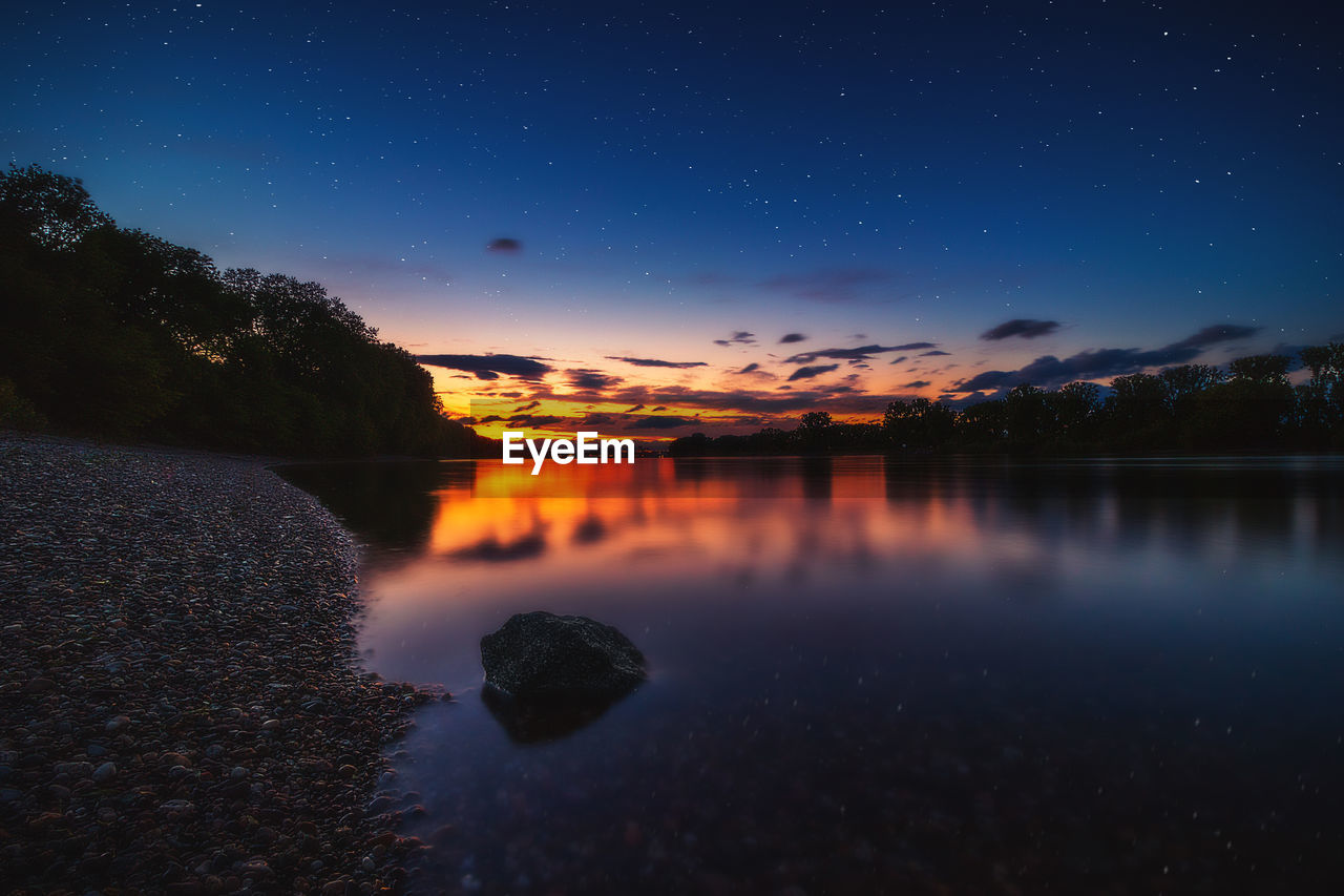 sky, water, scenics - nature, beauty in nature, tranquil scene, tranquility, reflection, night, no people, idyllic, nature, sunset, tree, lake, star - space, plant, waterfront, blue, orange color, outdoors, astronomy