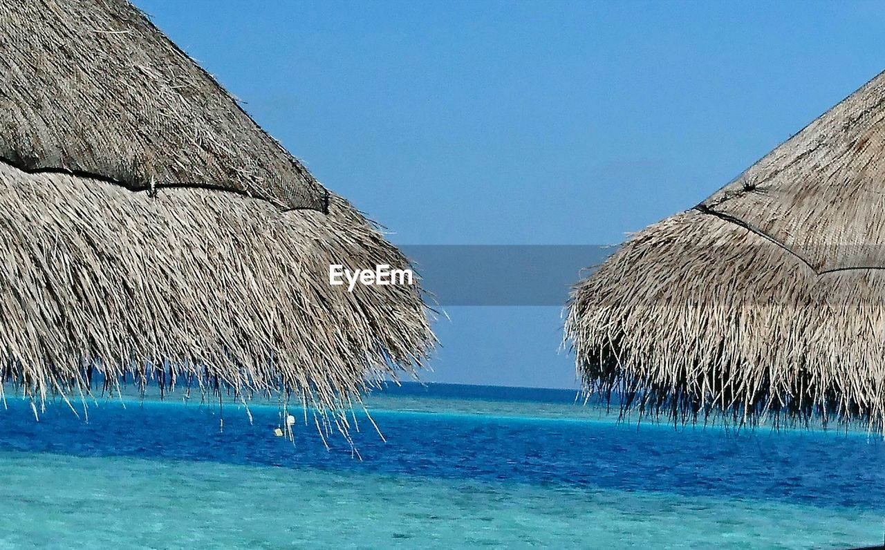 blue, sea, water, clear sky, beauty in nature, nature, scenics, tranquility, tranquil scene, day, outdoors, no people, thatched roof, horizon over water, beach, sky