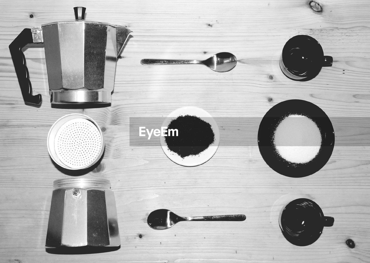High Angle View Of Tea Cups, Spoons And Kettle On Table