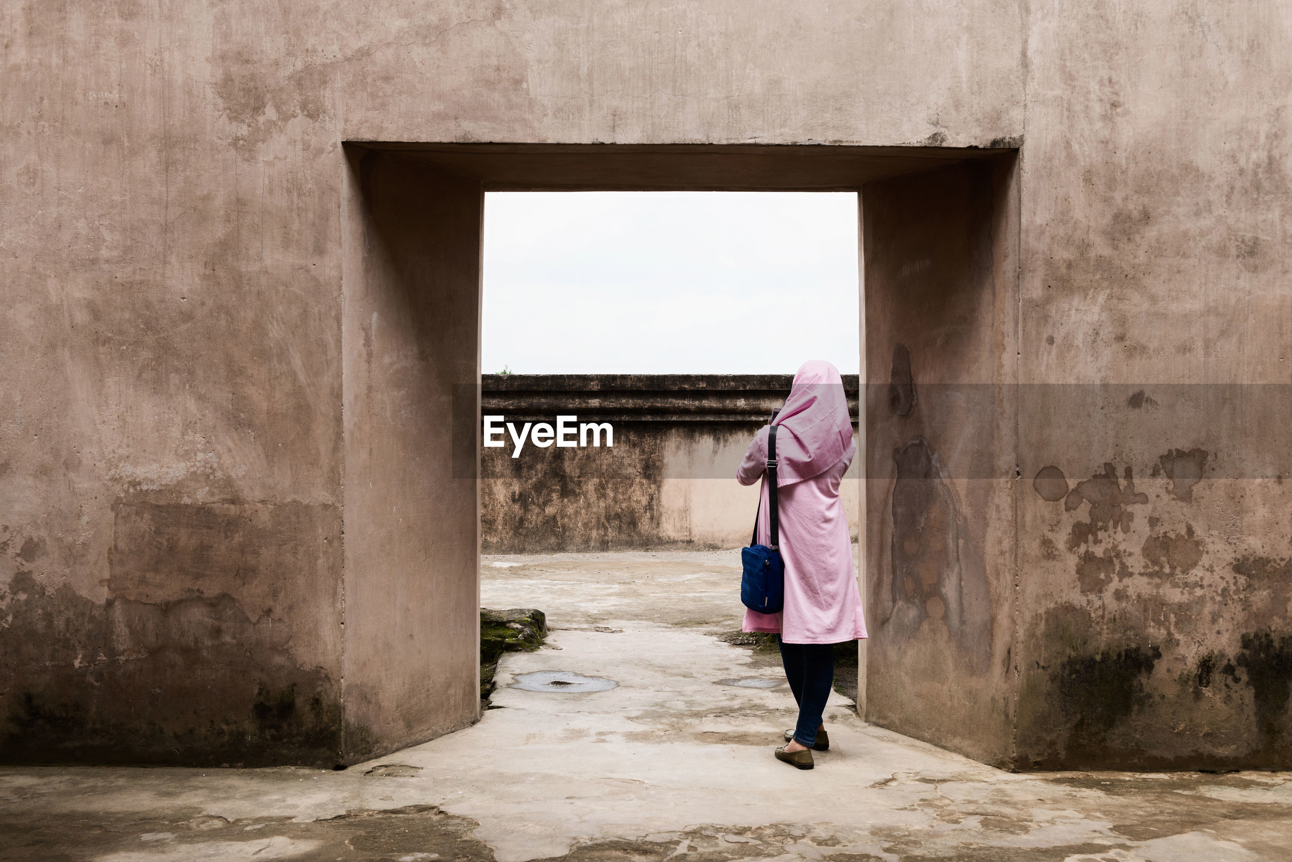 Rear view of woman in hijab standing against wall