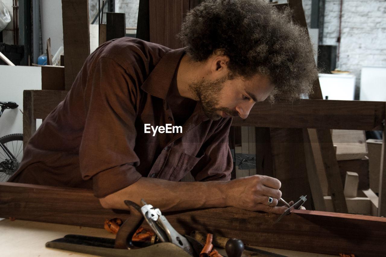 Carpenter measuring wooden plank at workshop