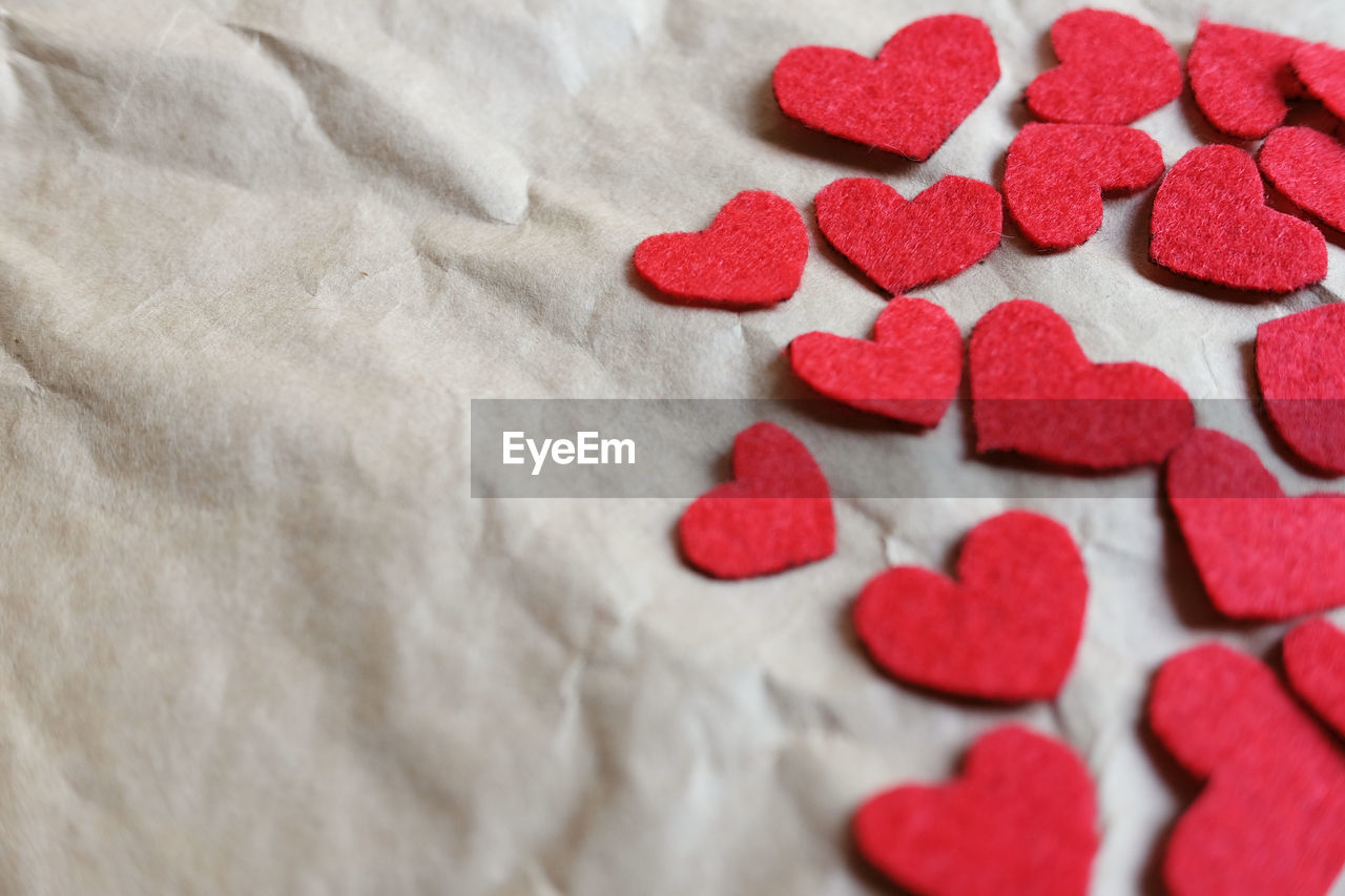 heart shape, positive emotion, love, indoors, still life, red, no people, sweet food, close-up, emotion, white color, food and drink, candy, food, textile, sweet, high angle view, art and craft, freshness, selective focus, temptation, candy heart, valentine's day - holiday