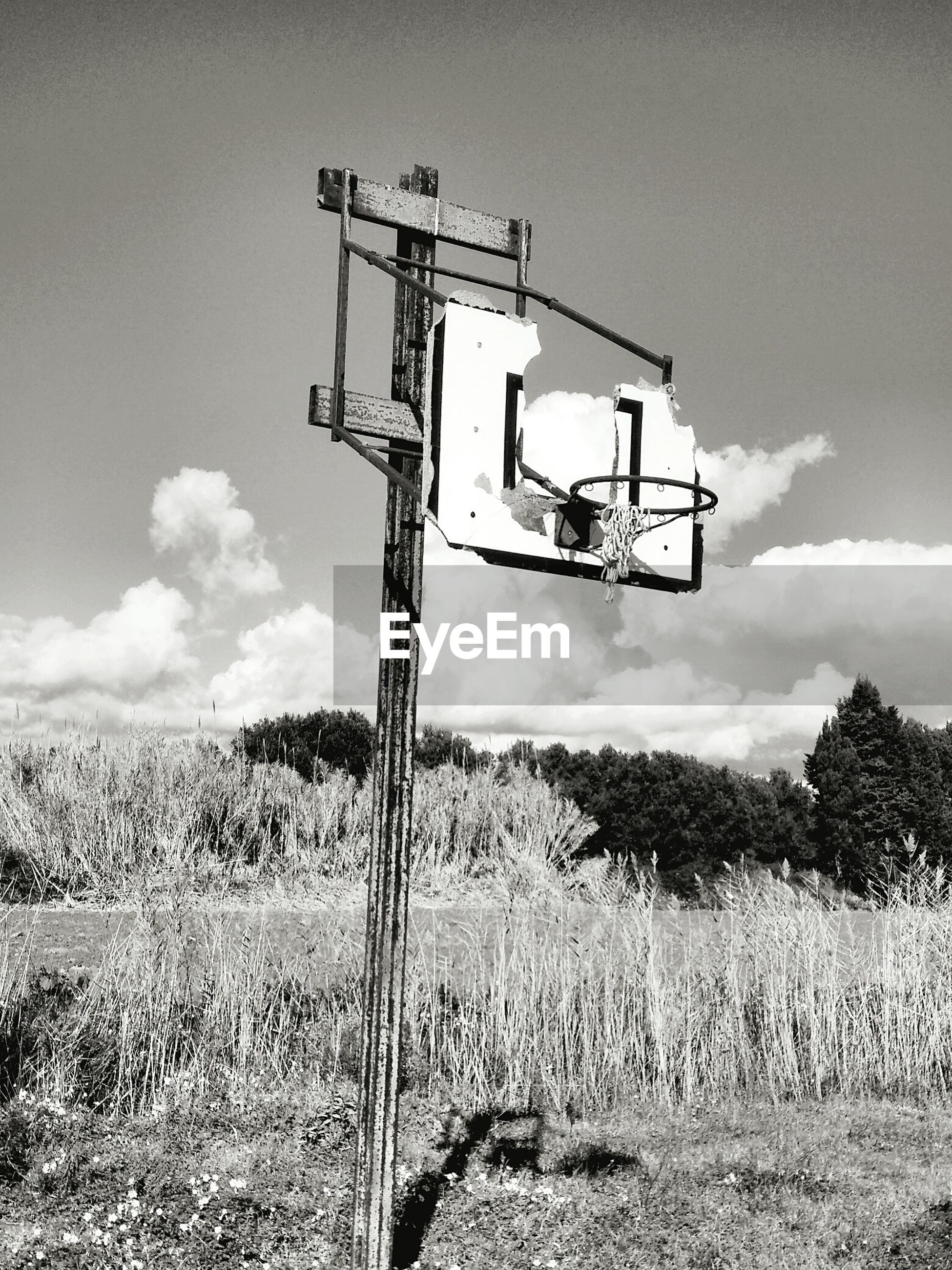 Low angle view of old basketball hoop on field against sky