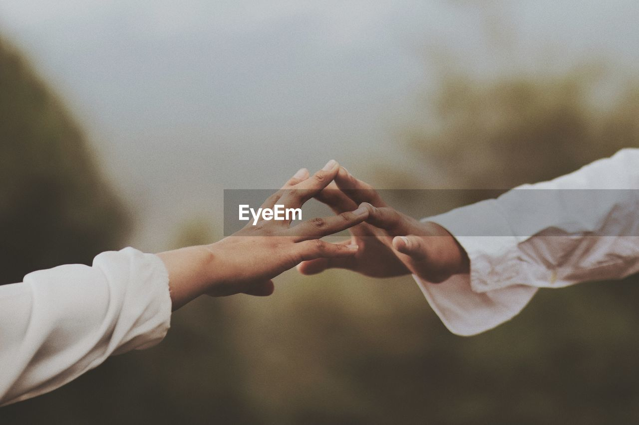 Cropped Image Of Couple Touching Each Others Hand