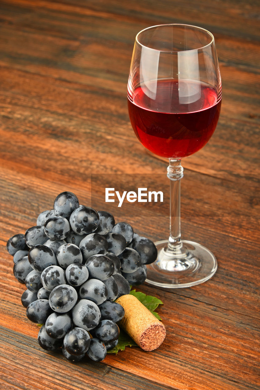 High angle view of red wine by grapes on wooden table