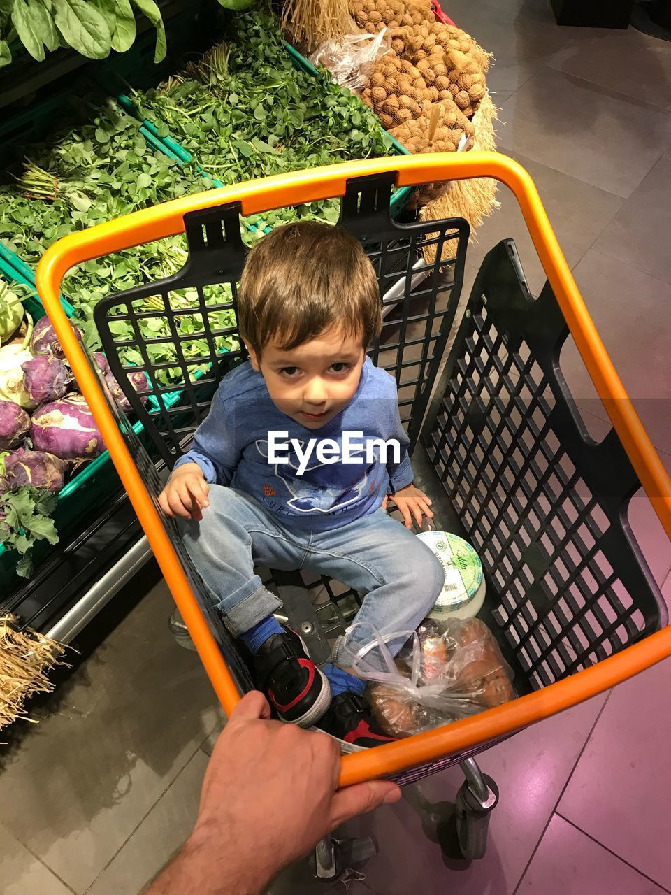 High angle portrait of cute boy sitting in shopping cart